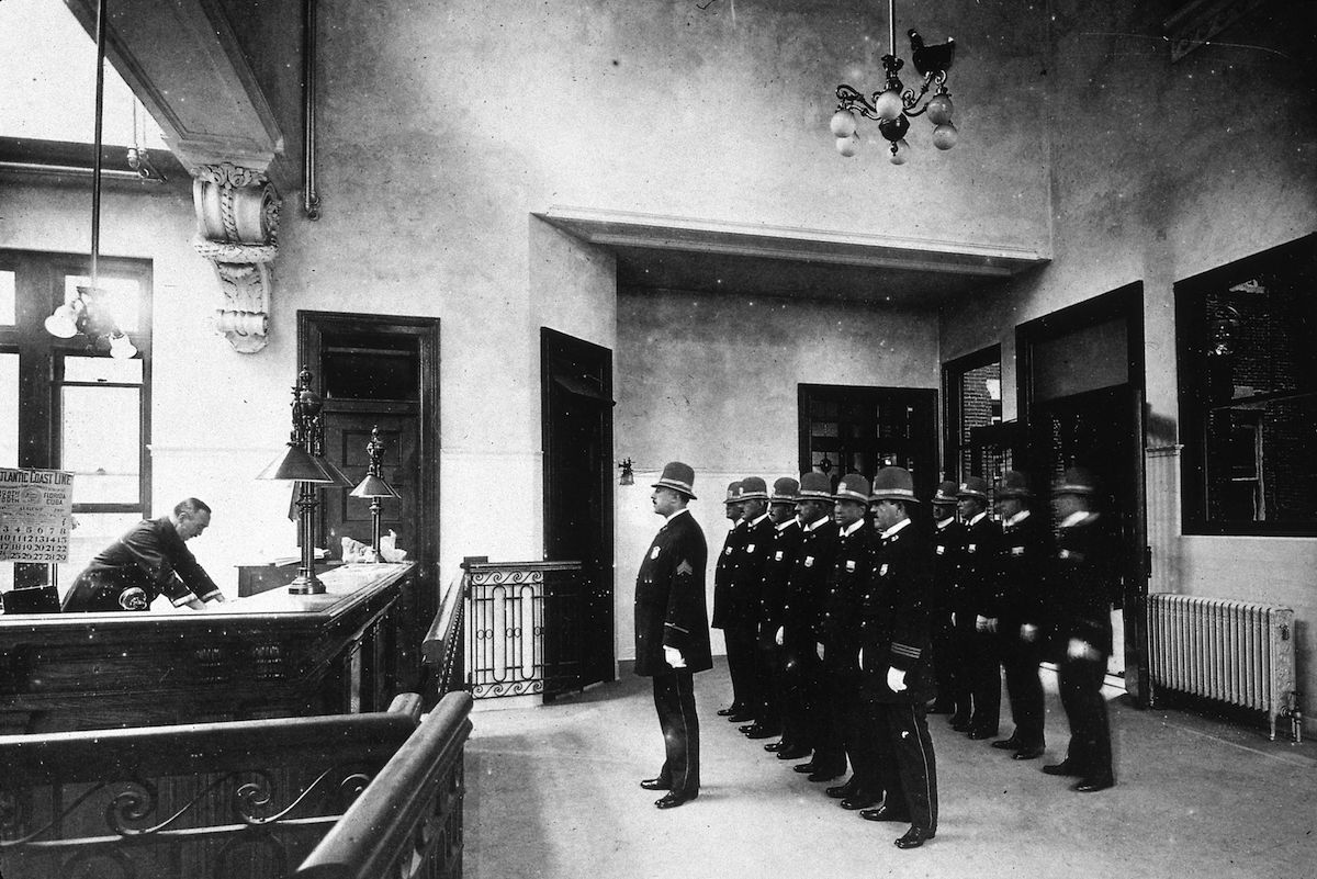 Uniformed police stand to attention behind their sergeant in a New York Police Department roll call, circa 1900