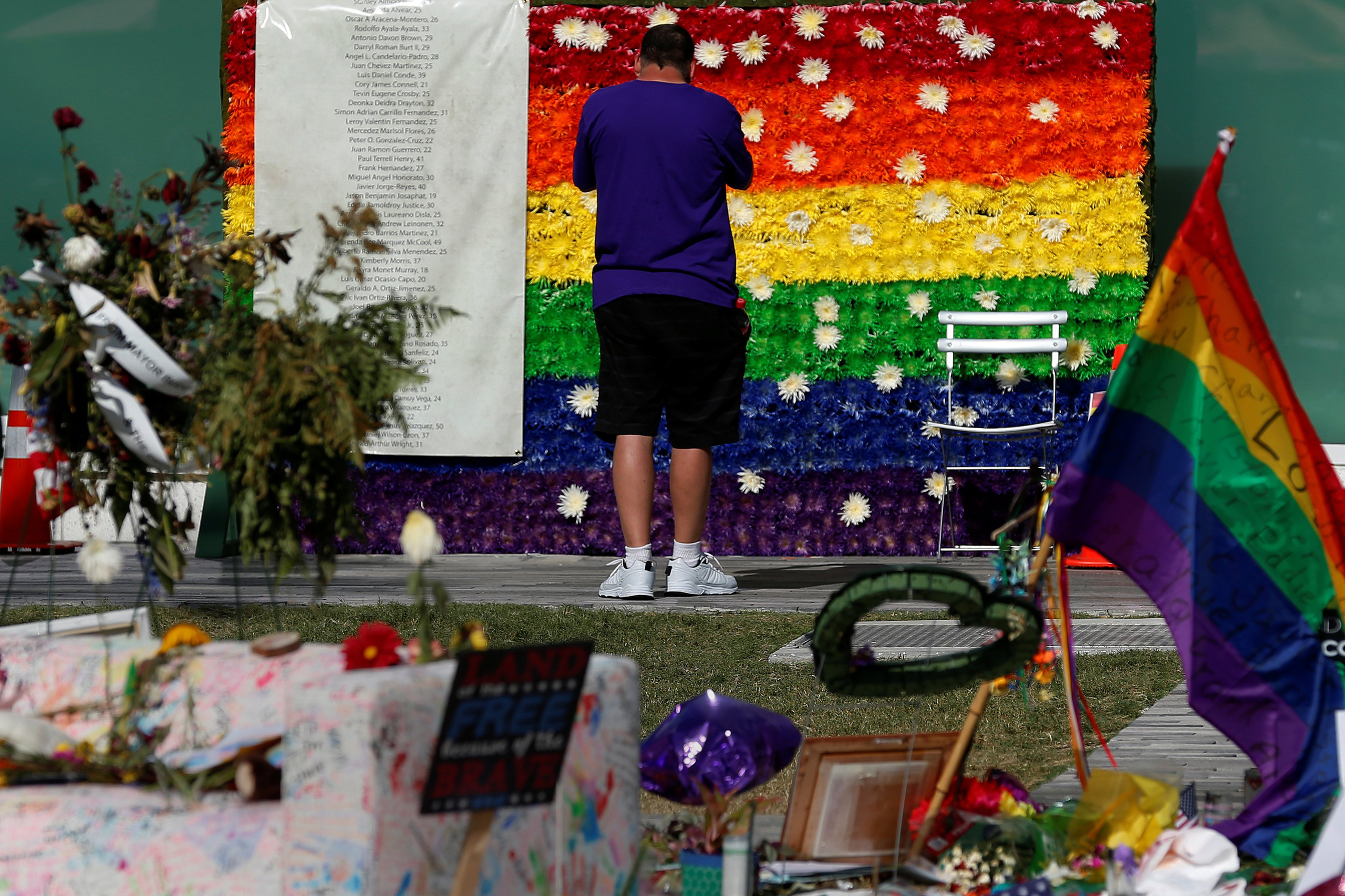 A man pays respect at a rainbow flower wall as part of the makeshift memorial for the Pulse nightclub mass shooting victims last week in Orlando, on June 21, 2016.