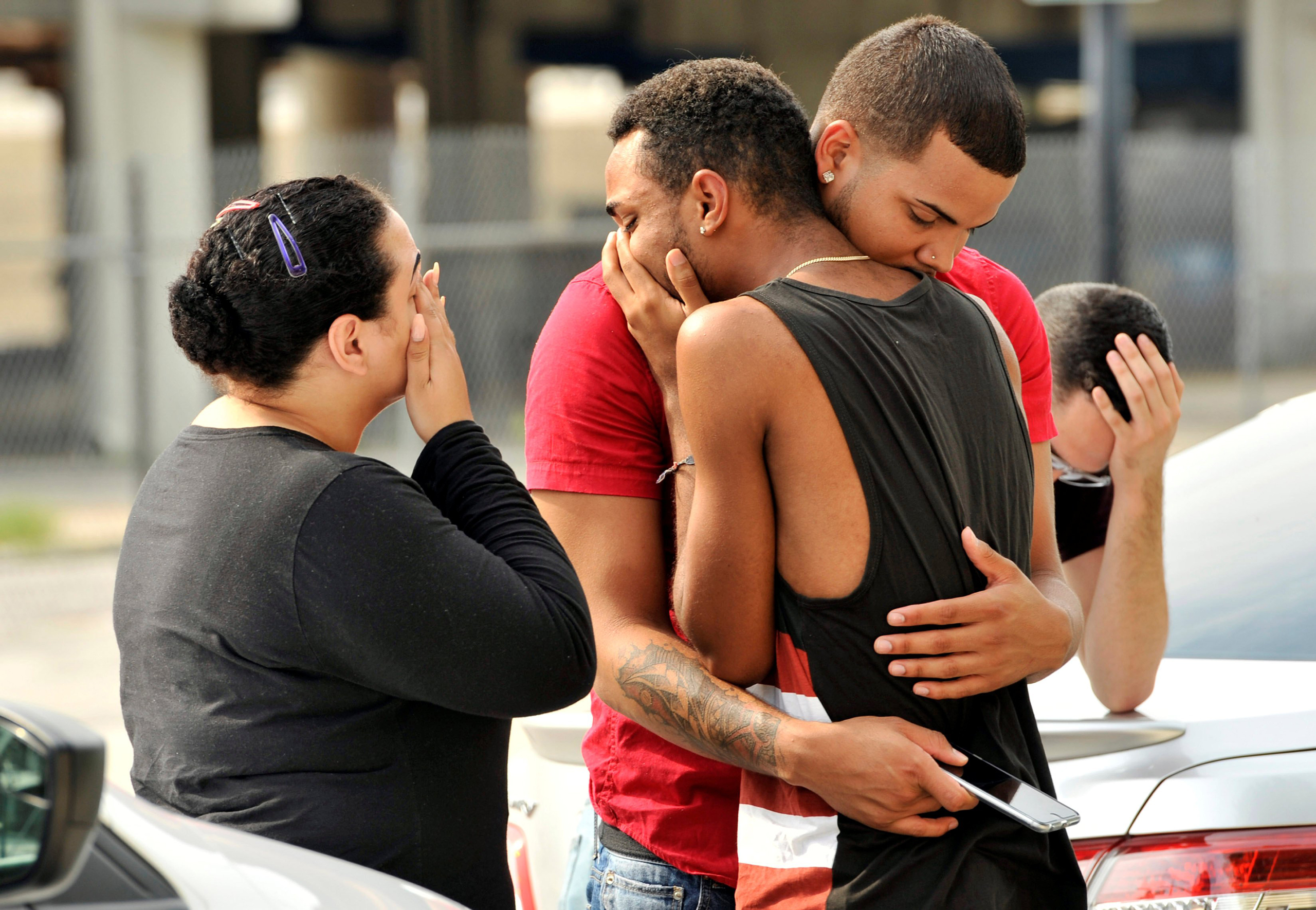 Friends and family members embrace outside the Orlando Police Headquarters during the investigation of a shooting at the Pulse nightclub in Orlando, Fla., on June 13, 2016.