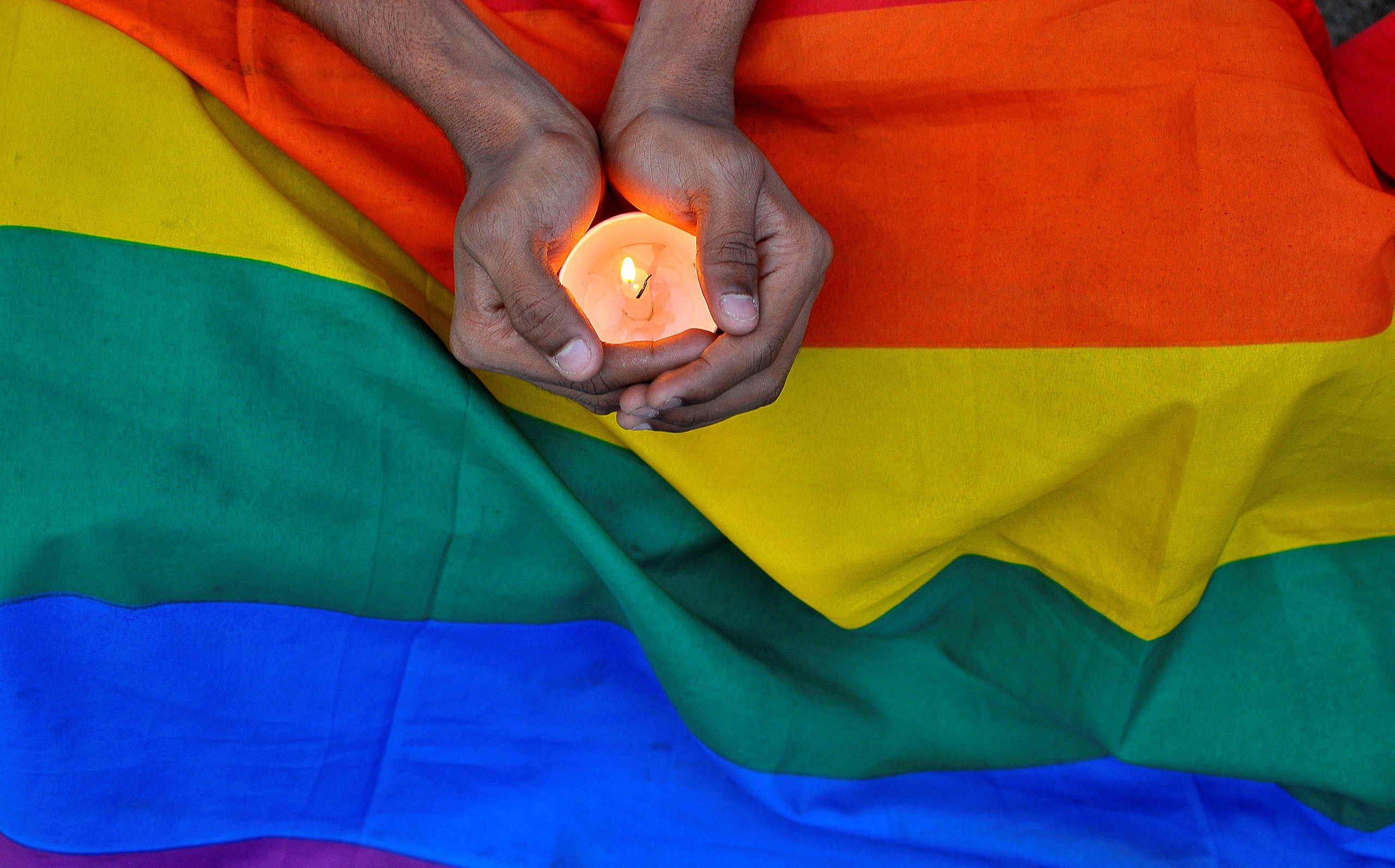 A member of the LGBT community in Bengalaru holds a candle during a memorial service following a mass shooting at the Pulse gay nightclub in Orlando, in India June 14, 2016.