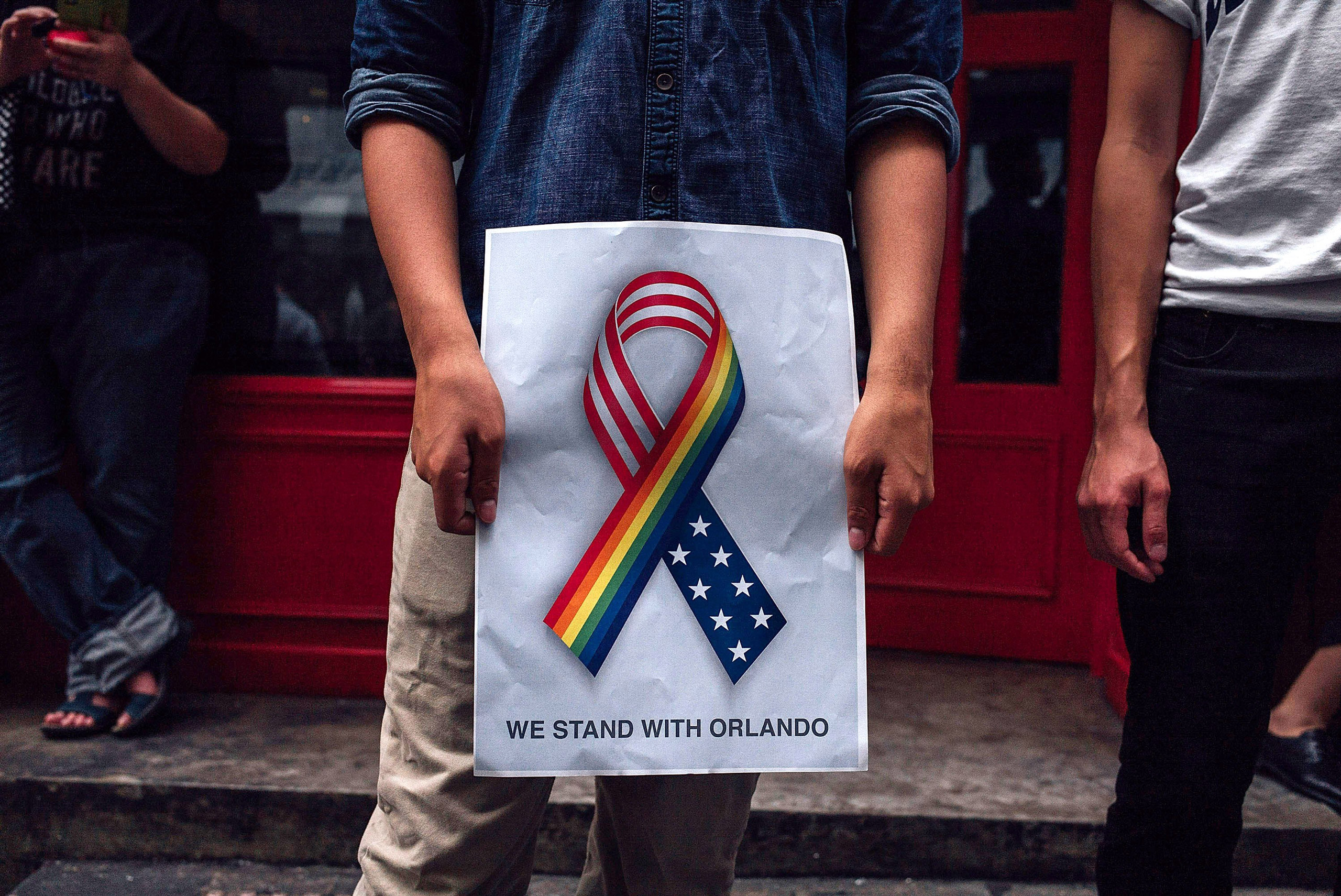 A man holds up a 'we stand together with Orlando' poster as people take part in a candlelight vigil for the victims of a shooting in a gay nightclub in Orlando, Fla., in Hong Kong on June 13, 2016 .