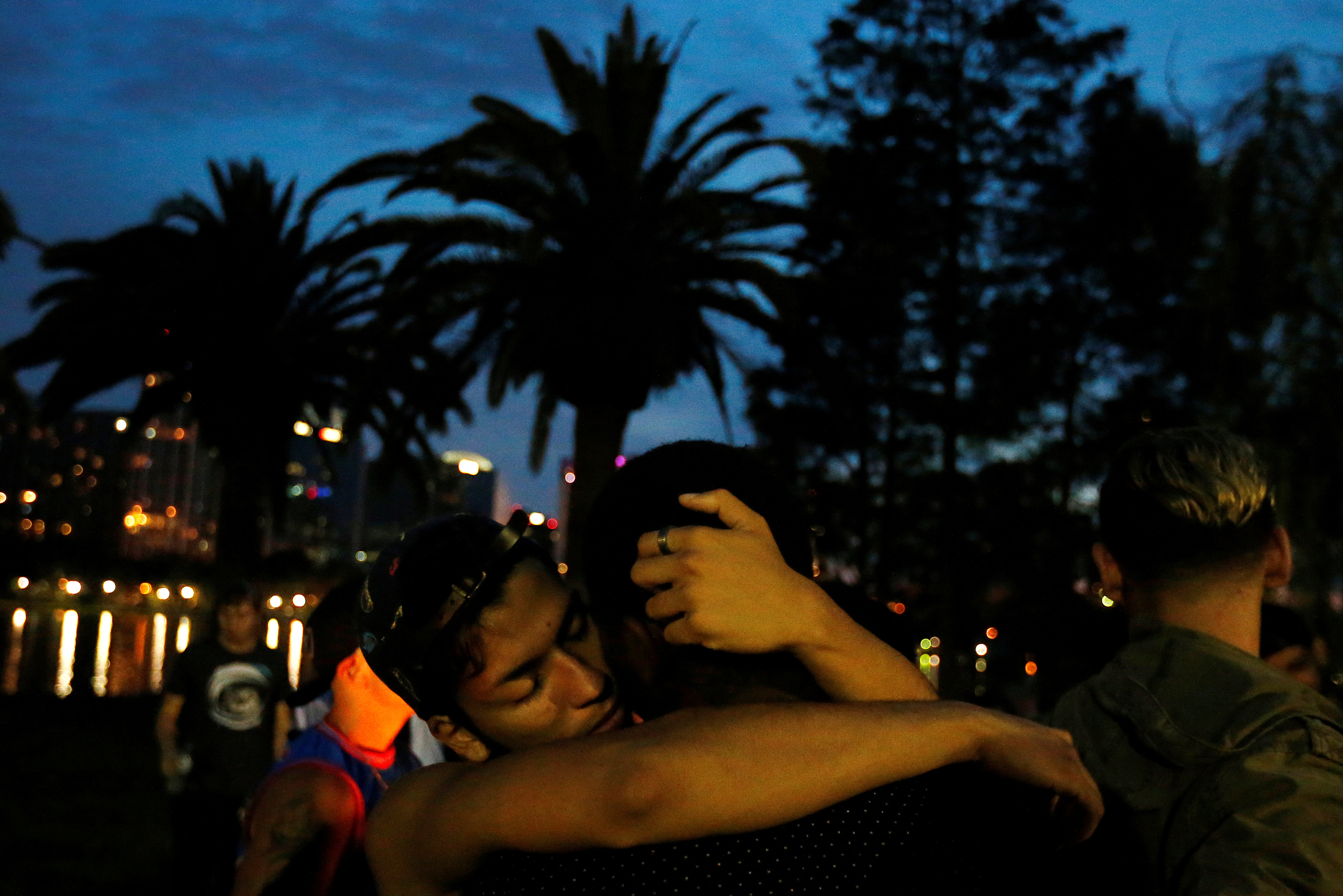 Men hug during a vigil in a park following a mass shooting at the Pulse gay nightclub in Orlando Fla., on June 12, 2016.