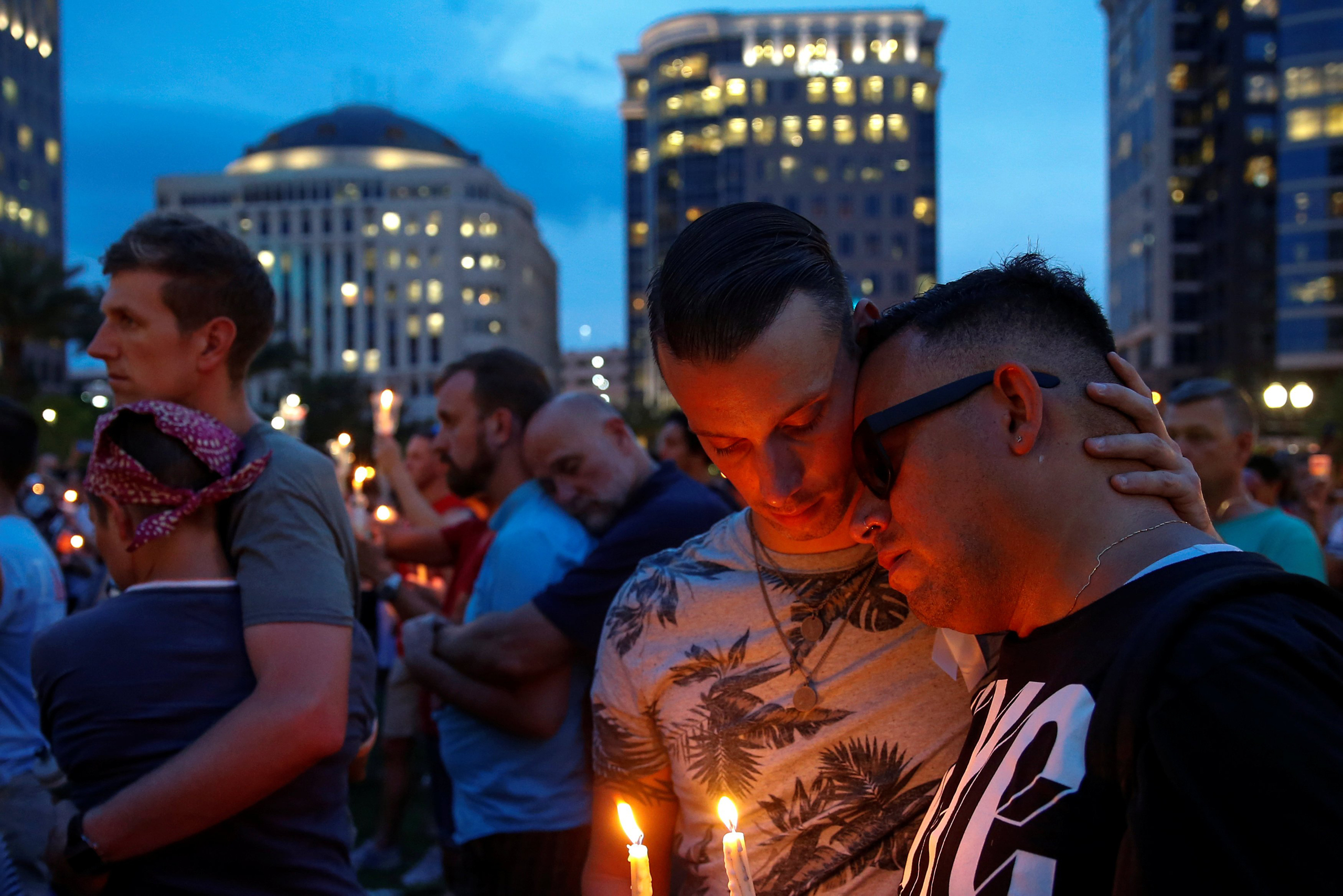 Men embrace during a candle light vigil in memory of victims one day after a mass shooting at the Pulse gay night club in Orlando on June 13, 2016.