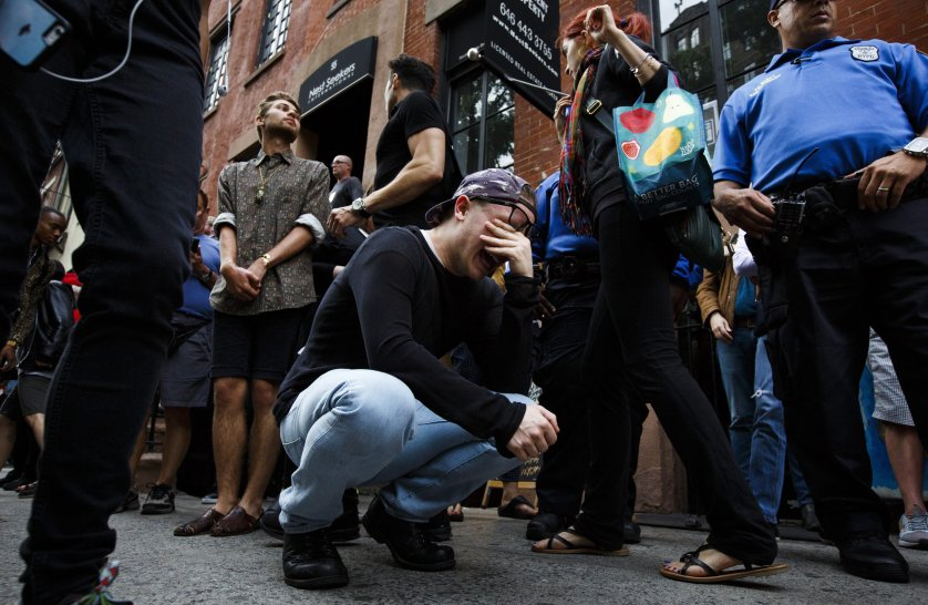 Taylor Forrest (C), of Orlando, Florida, cries on the sidewalk near a memorial for the victims of a mass shooting at a gay club in Orlando outside of the Stonewall Inn, a famous gay bar, in New York City on June 13, 2016.