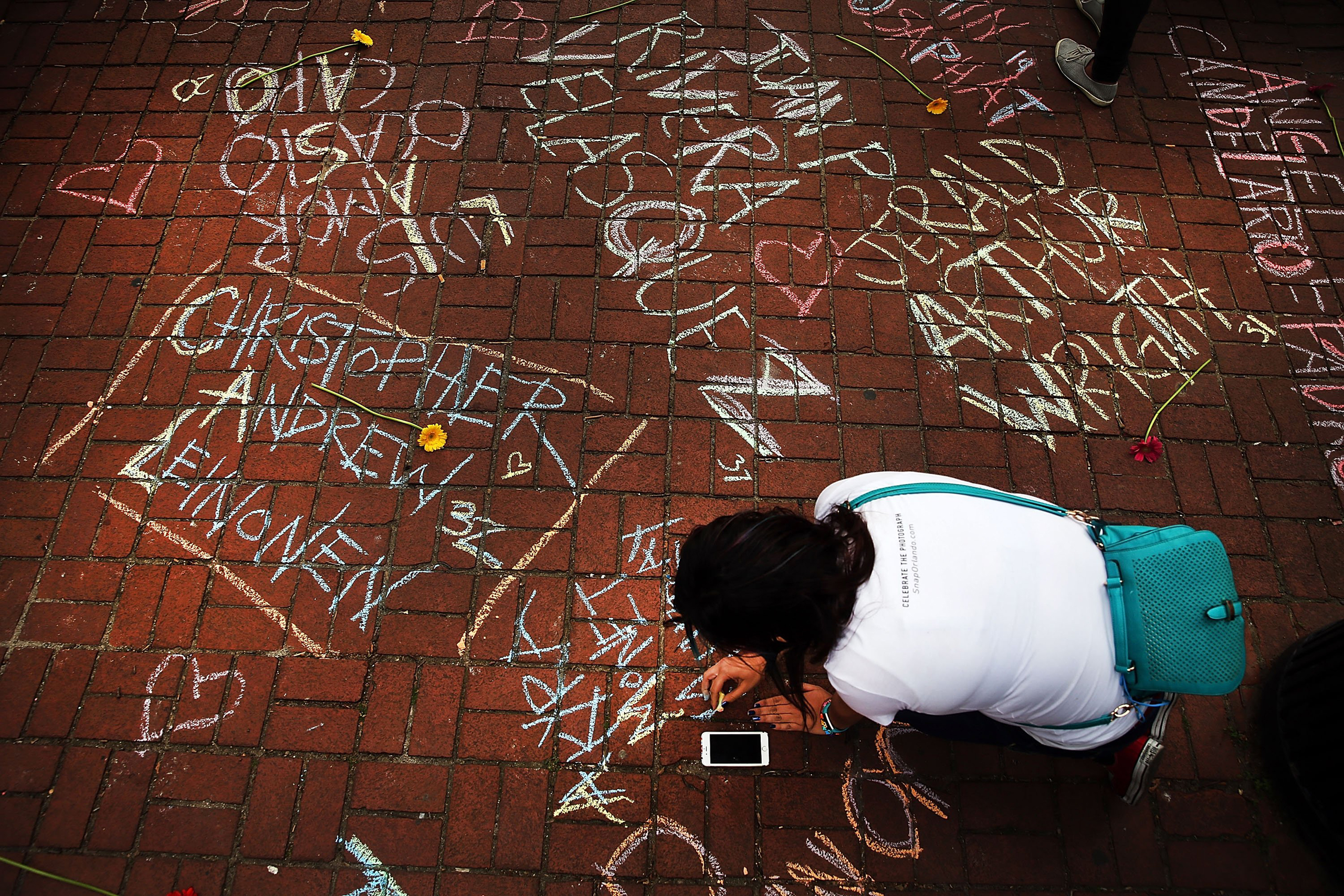 A woman joins others in writing the names of shooting victims in chalk in a park across from the iconic New York City gay and lesbian bar The Stonewall Inn on June 13, 2016.