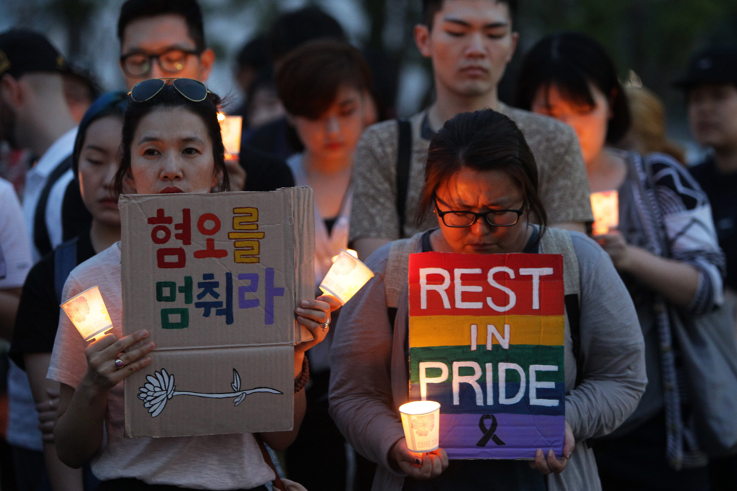 People gather during a vigil in downtown Seoul to remember victims of the shooting at an Orlando nightclub, in Seoul, South Korea, on June 13, 2016.