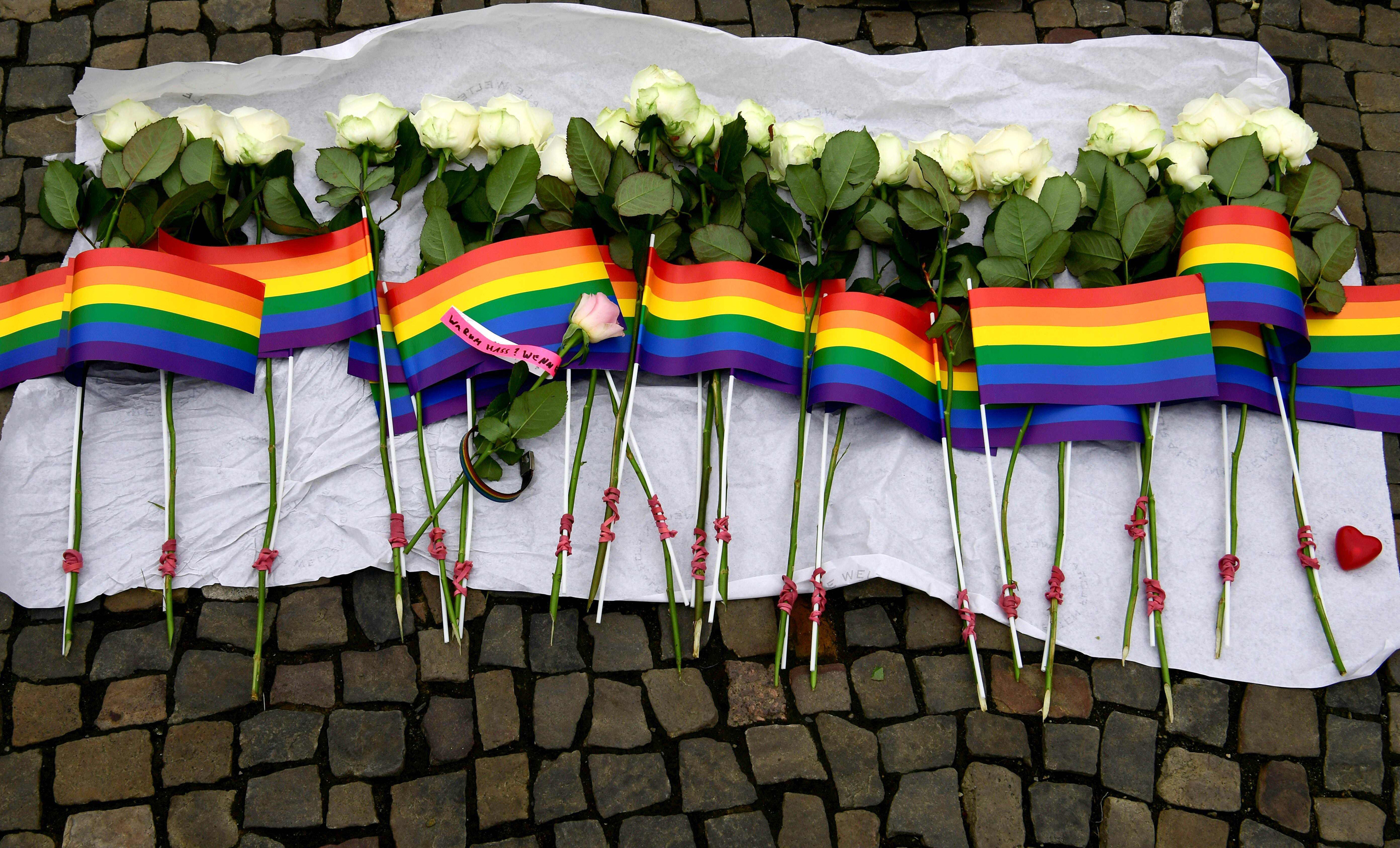 White roses and rainbow flags are displayed in front of the U.S. Embassy in Berlin on June 13, 2016.