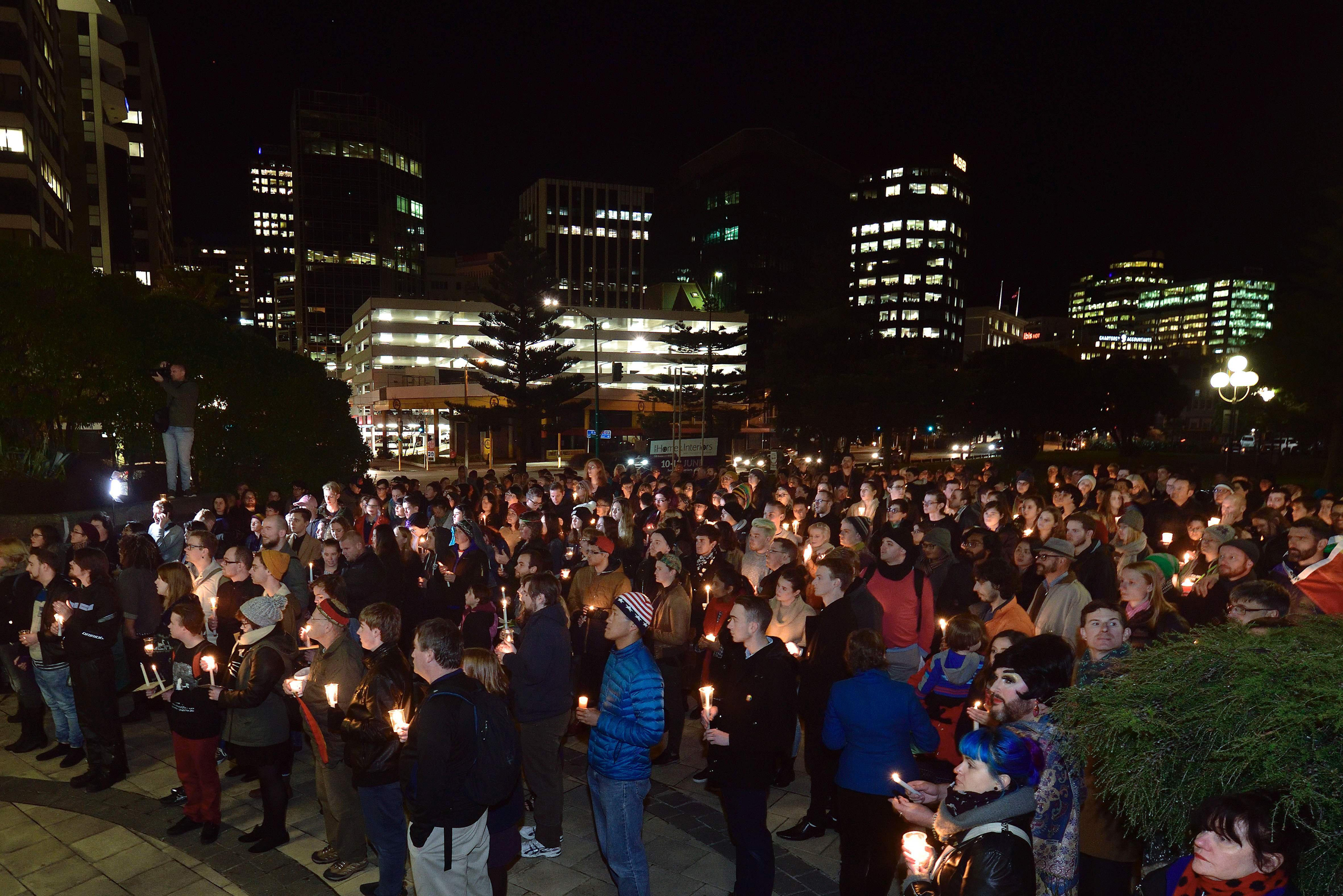 Participants hold candles during a vigil at Frank Kitts Park  in remembrance of victims after a gunman opened fire at an Orlando nightclub, in Wellington, New Zealand on June 13, 2016.
