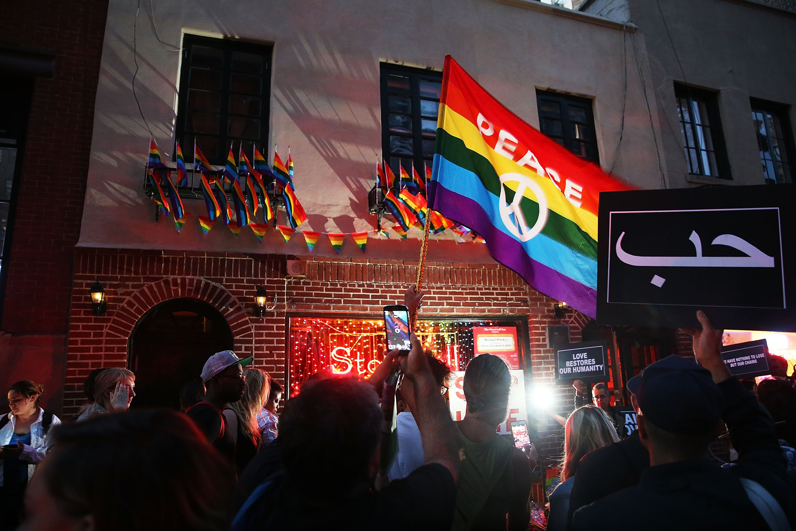 Mourners gather outside of the iconic New York City gay and lesbian bar the Stonewall Inn to light candles, lay flowers and grieve for those killed in Orlando on June 12, 2016.