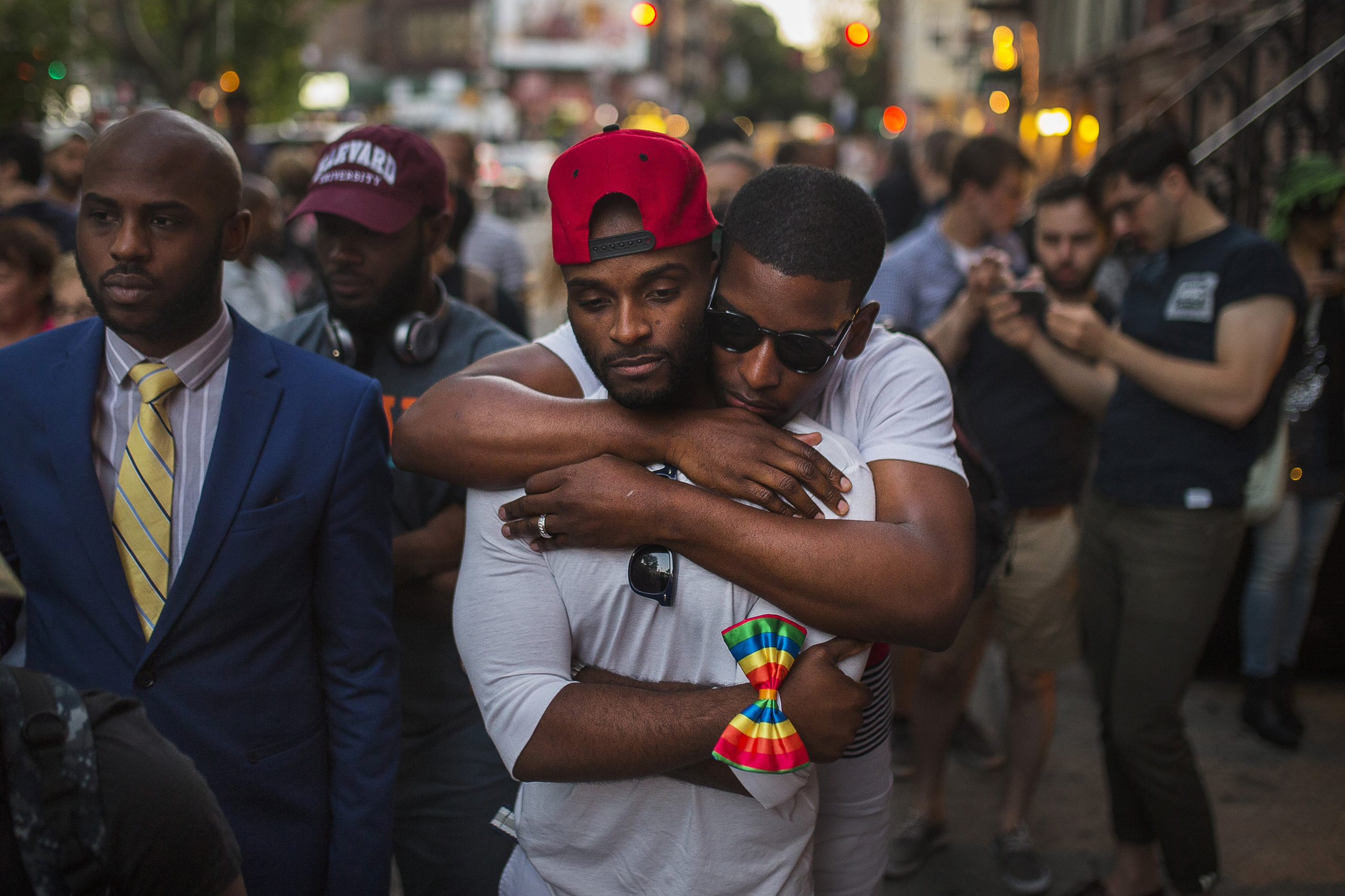 A couple embraces as people gather in front of a makeshift memorial to the victims of a mass shooting at a gay nightclub in Orlando, in New York City on June 12, 2016.