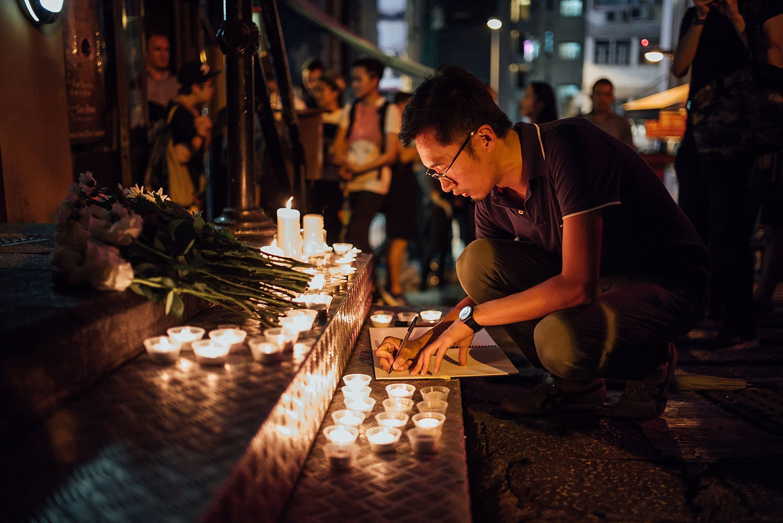 People take part in a candlelight vigil for the victims of a shooting in a gay nightclub in Orlando, in Hong Kong on June 13, 2016.