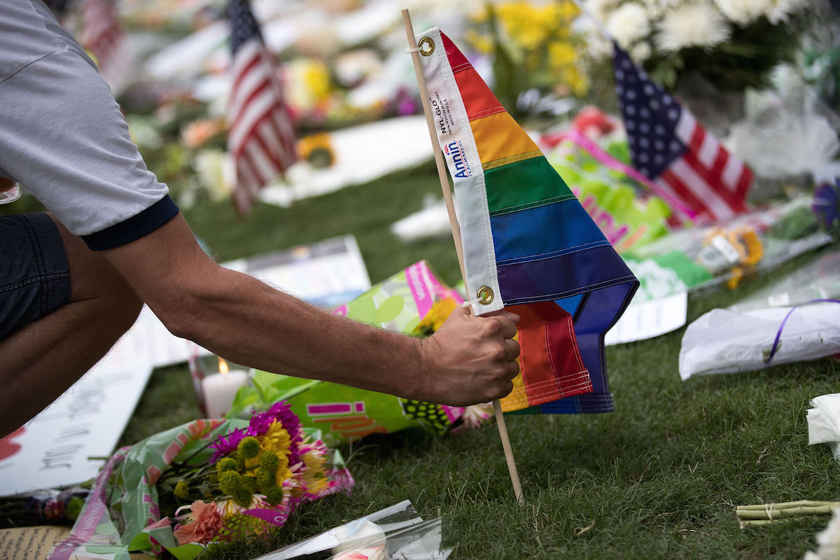 A man plants a Pride flag at a makeshift memorial prior to an evening vigil for the victims of the Pulse Nightclub shootings, at the Dr. Phillips Center for the Performing Arts, June 13, 2016 in Orlando, Fla.