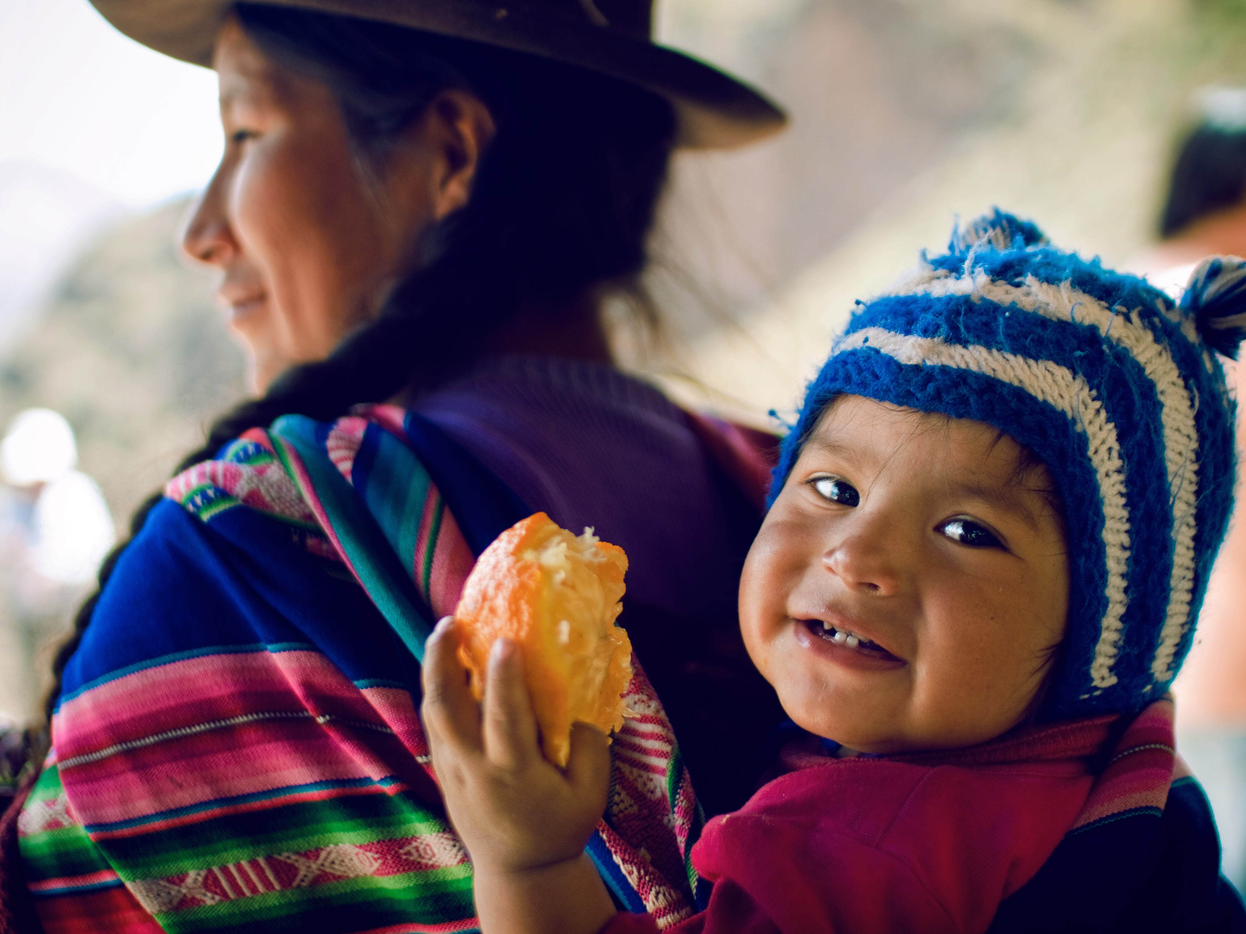 A children and her mother, wearing typical Andean wool dresses and hats, nearby the ruins of P?sac, Valle de los Incas, Peru