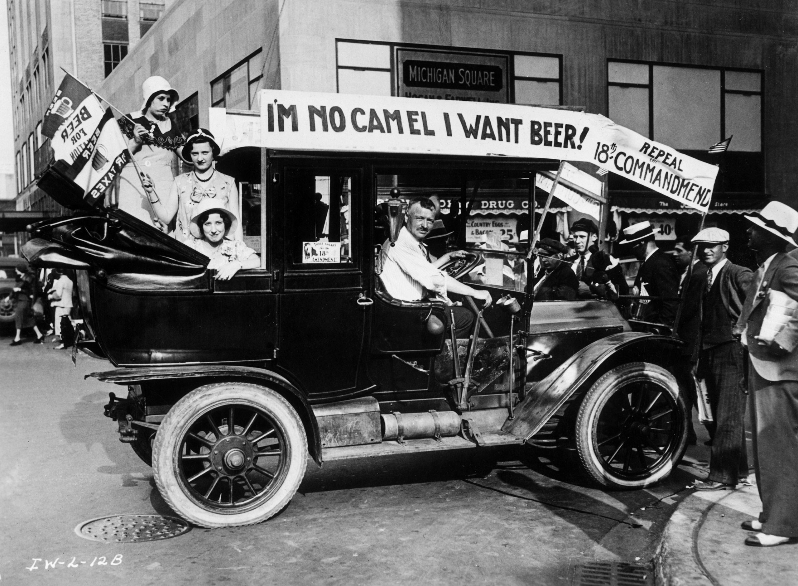 Prohibition protesters parade in a car emblazoned with signs and flags calling for the repeal of the 18th Amendment.
