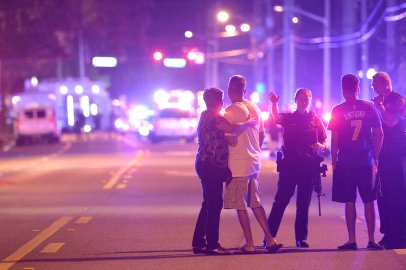Police officers direct family members away from a shooting at Pulse nightclub in Orlando, Fla., on June 12, 2016.