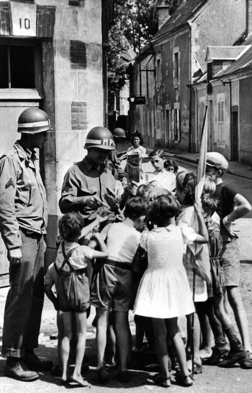 French children scramble around a sergeant, right, a US Army military policeman, as he breaks open a 'K' ration package for distribution in a street of Orleans