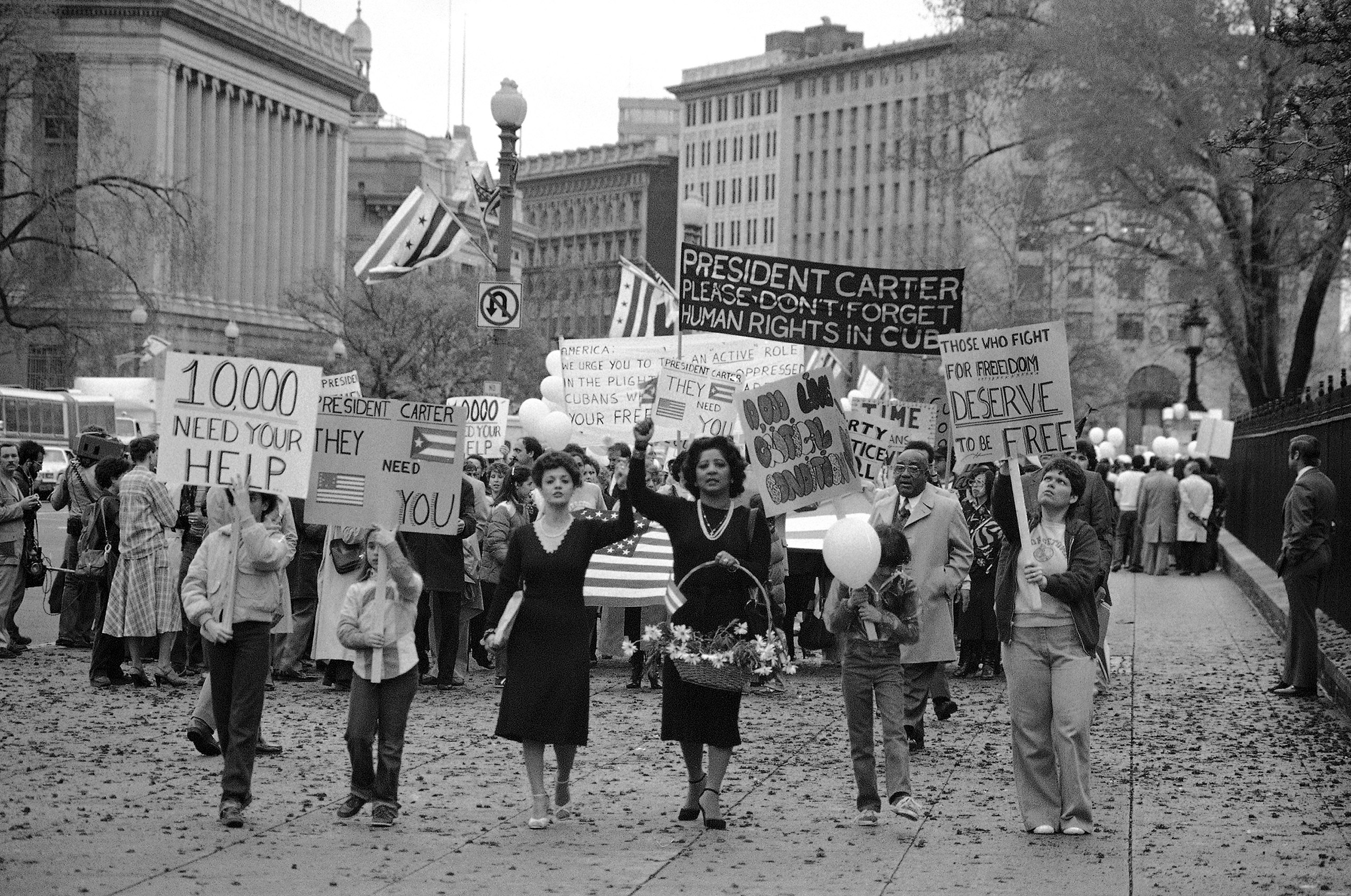 A group marches to the White House to thank President Jimmy Carter for his decision to admit 3,500 Cuban refugees from those at the Peruvian Embassy in Havana. Mrs. Violeta Mora of Chevy Chase, Md., presented the basket of flowers to a White House official for delivery to President Carter in Washington on Monday, April 14, 1980.