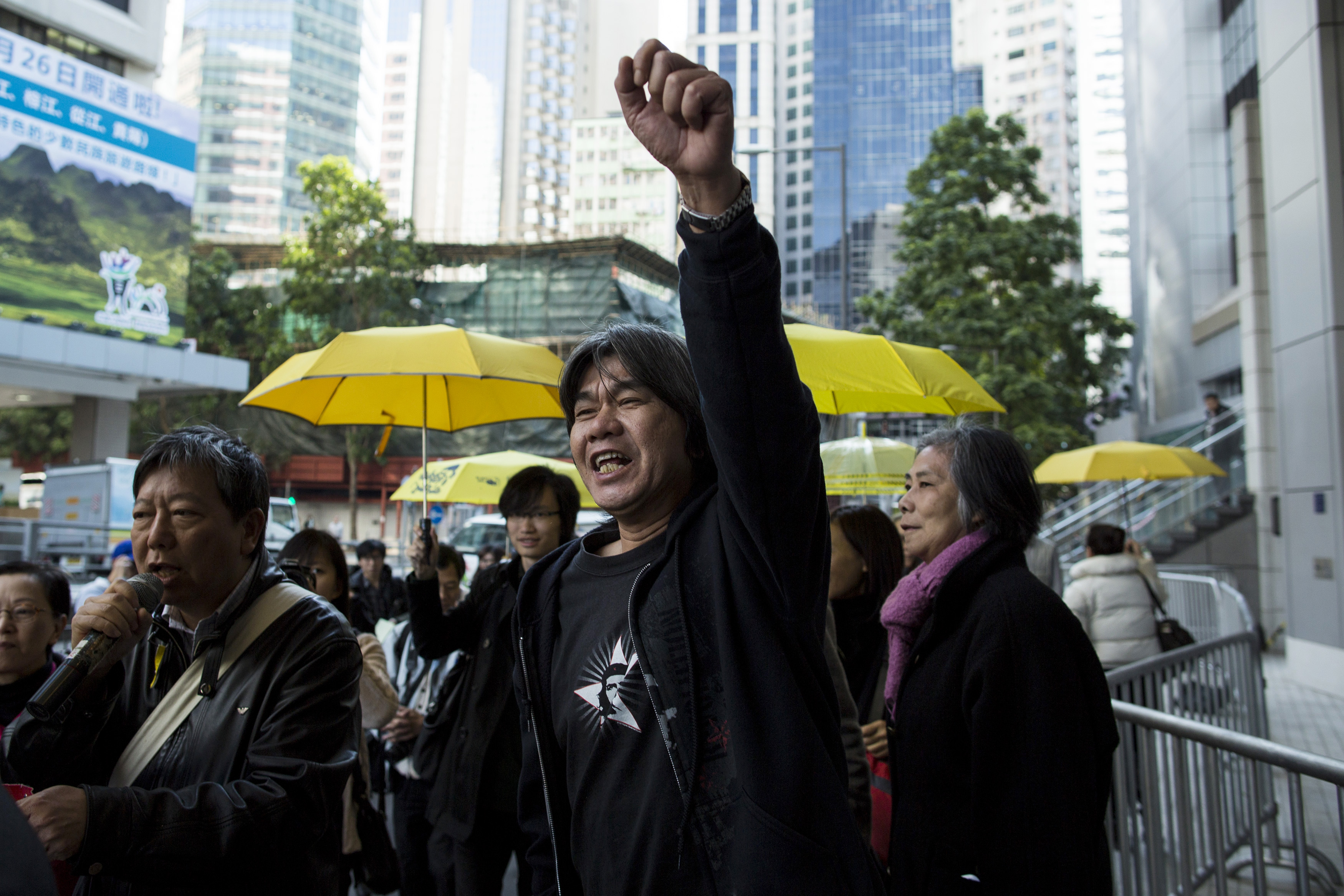 League of Social Democrats lawmaker Leung Kwok-hung, center, raises his fist and shouts slogans outside police headquarters in Hong Kong on Jan. 15, 2015