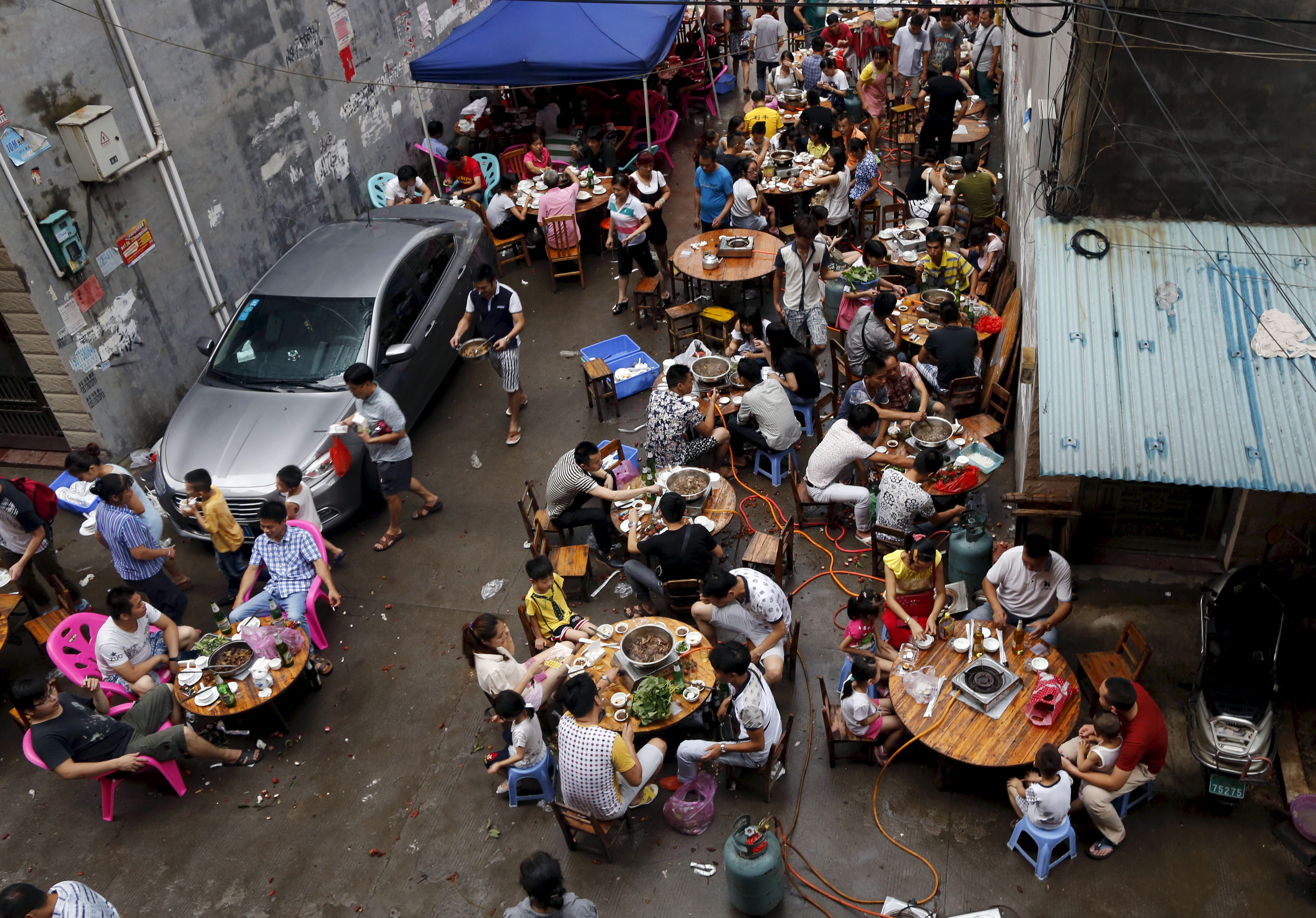 People eat dog meat at a dog-meat restaurant district during the Yulin Dog Meat Festival in the Chinese city of Yulin, Guangxi Zhuang Autonomous Region, on June 22, 2015