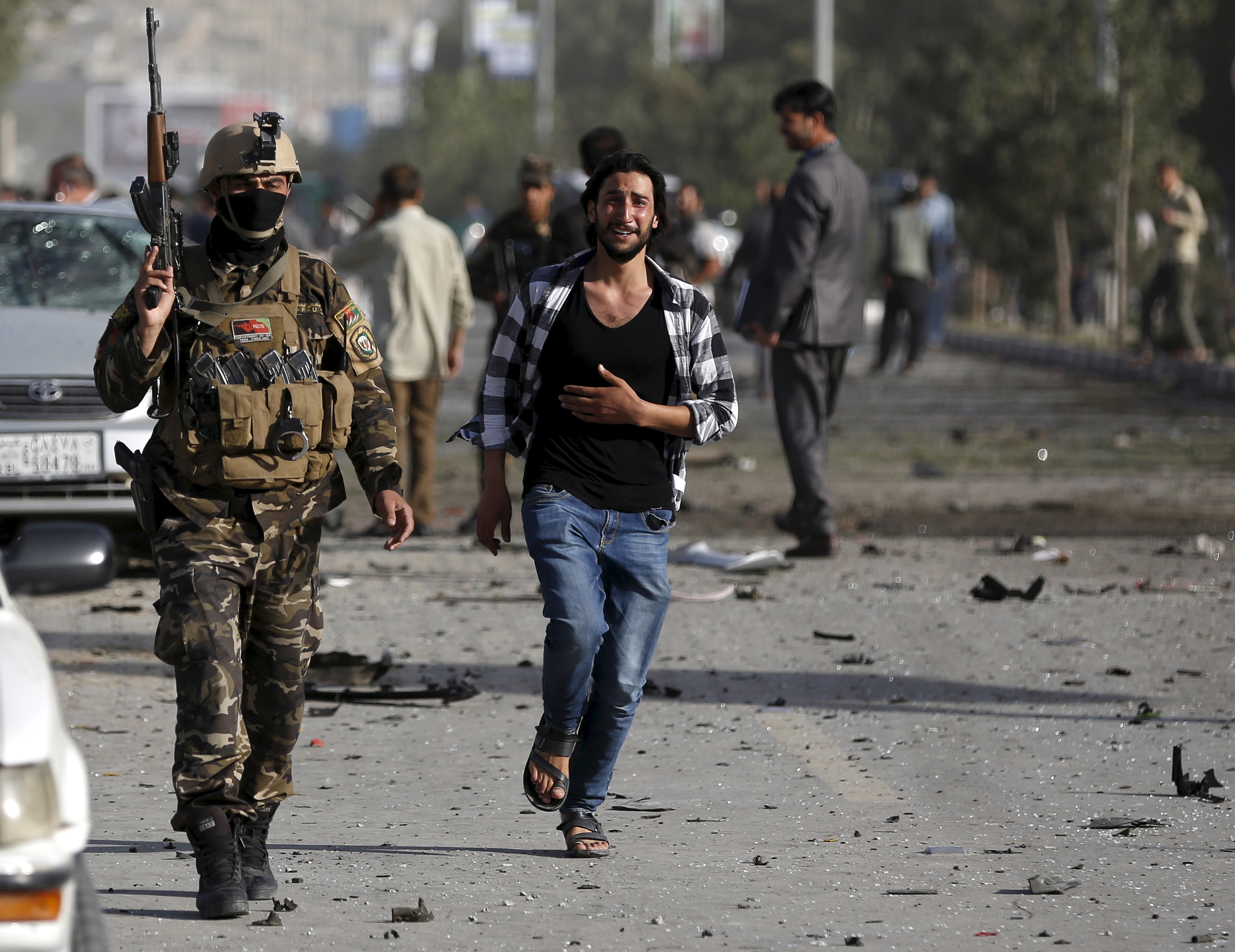An Afghan man weeps as he runs at the site of a car bomb blast in Kabul, Afghanistan Aug. 22, 2015
