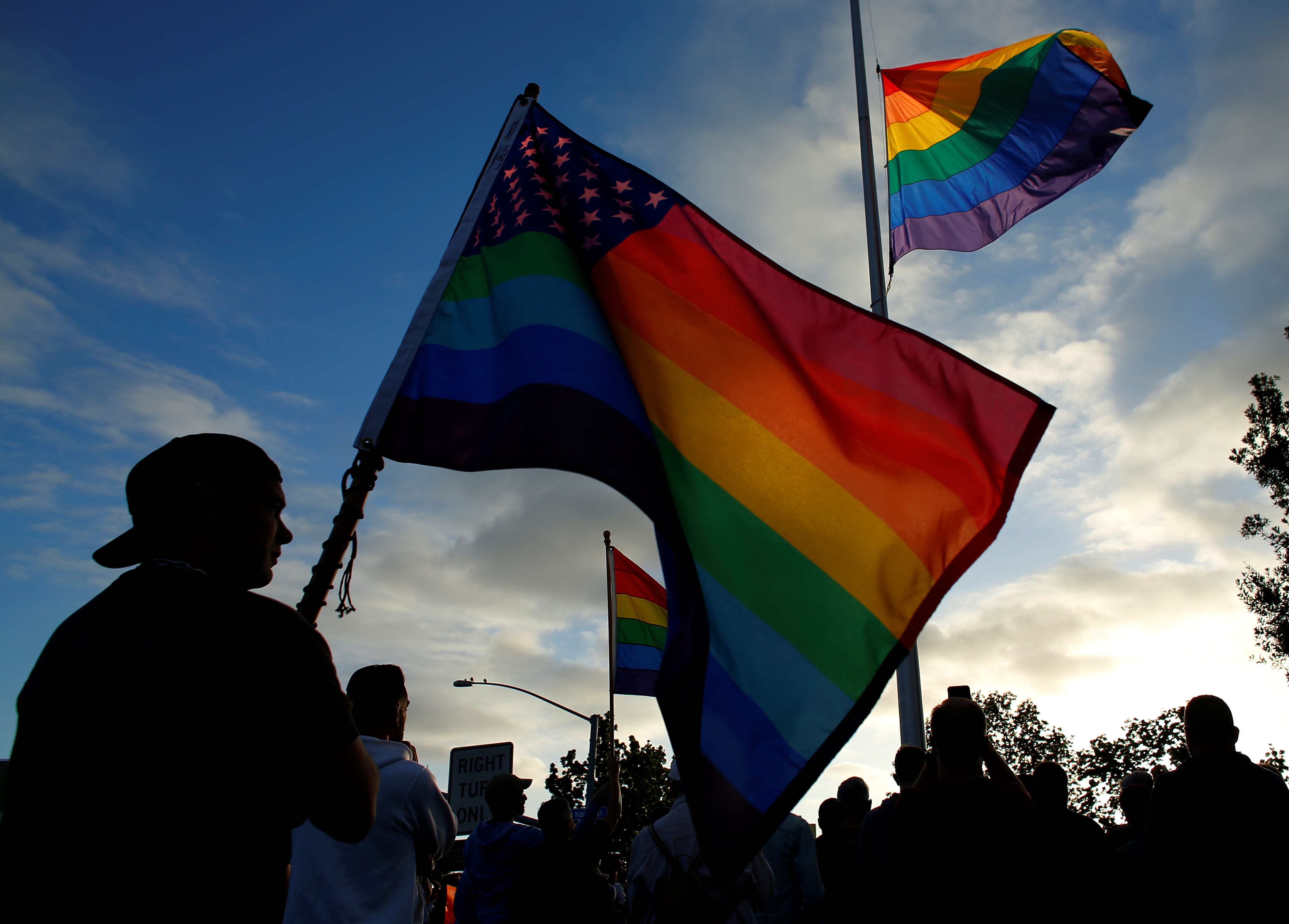 Mourners gather under an LGBT pride flag flying at half-mast for a candlelight vigil in remembrance for mass shooting victims in Orlando, from San Diego, California, U.S. June 12, 2016.