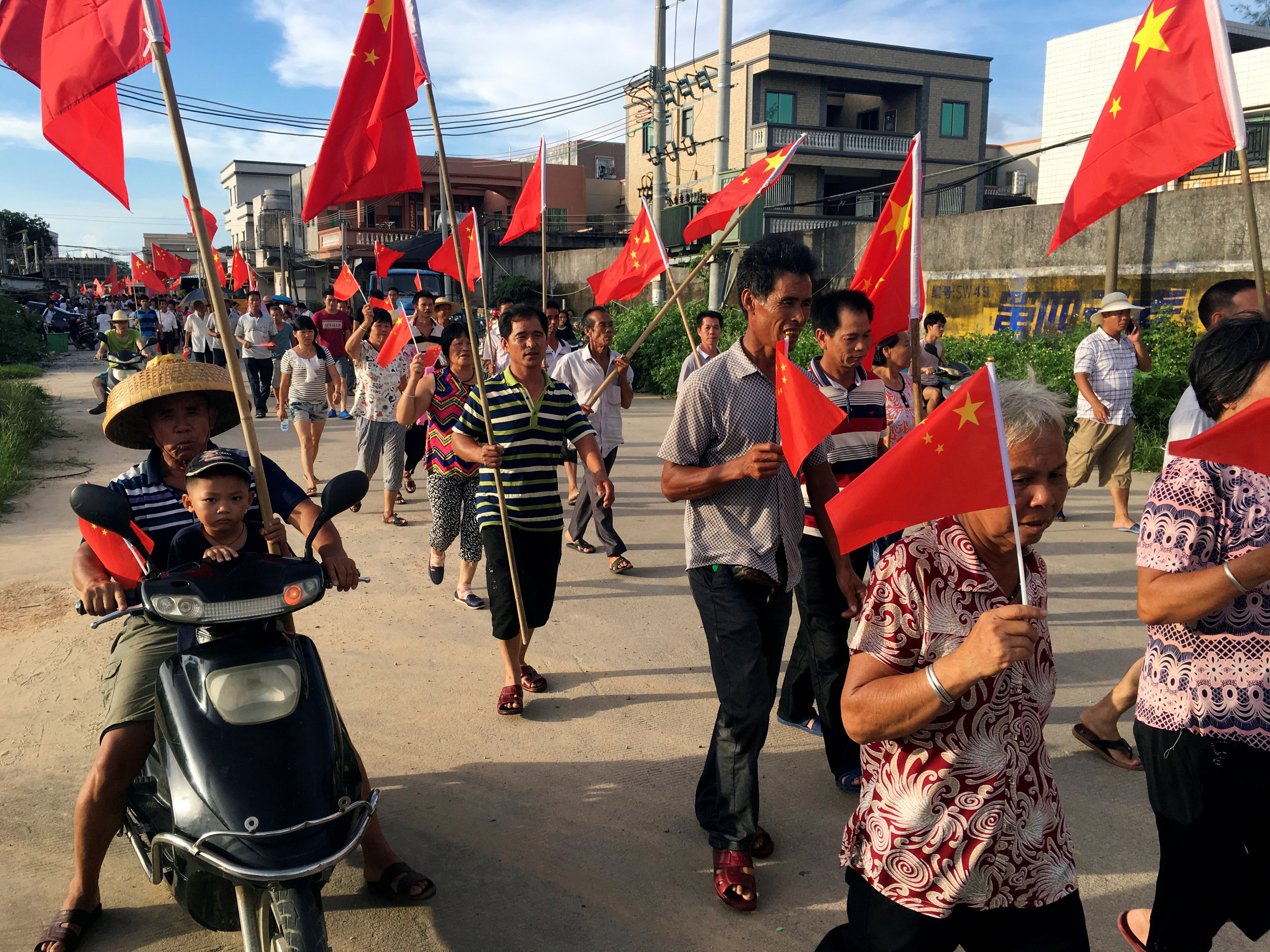 Villagers carrying Chinese national flags protest at Wukan village in China's Guangdong province June 20, 2016.
