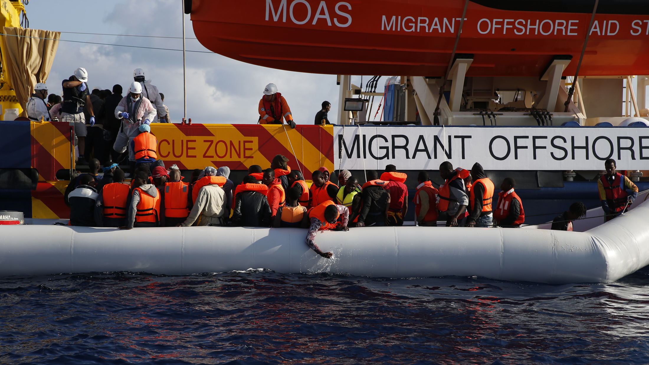 Migrants in a dinghy climb aboard the Migrant Offshore Aid Station (MOAS) ship Topaz Responder, some 20 nautical miles off the coast of Libya, June 23, 2016.