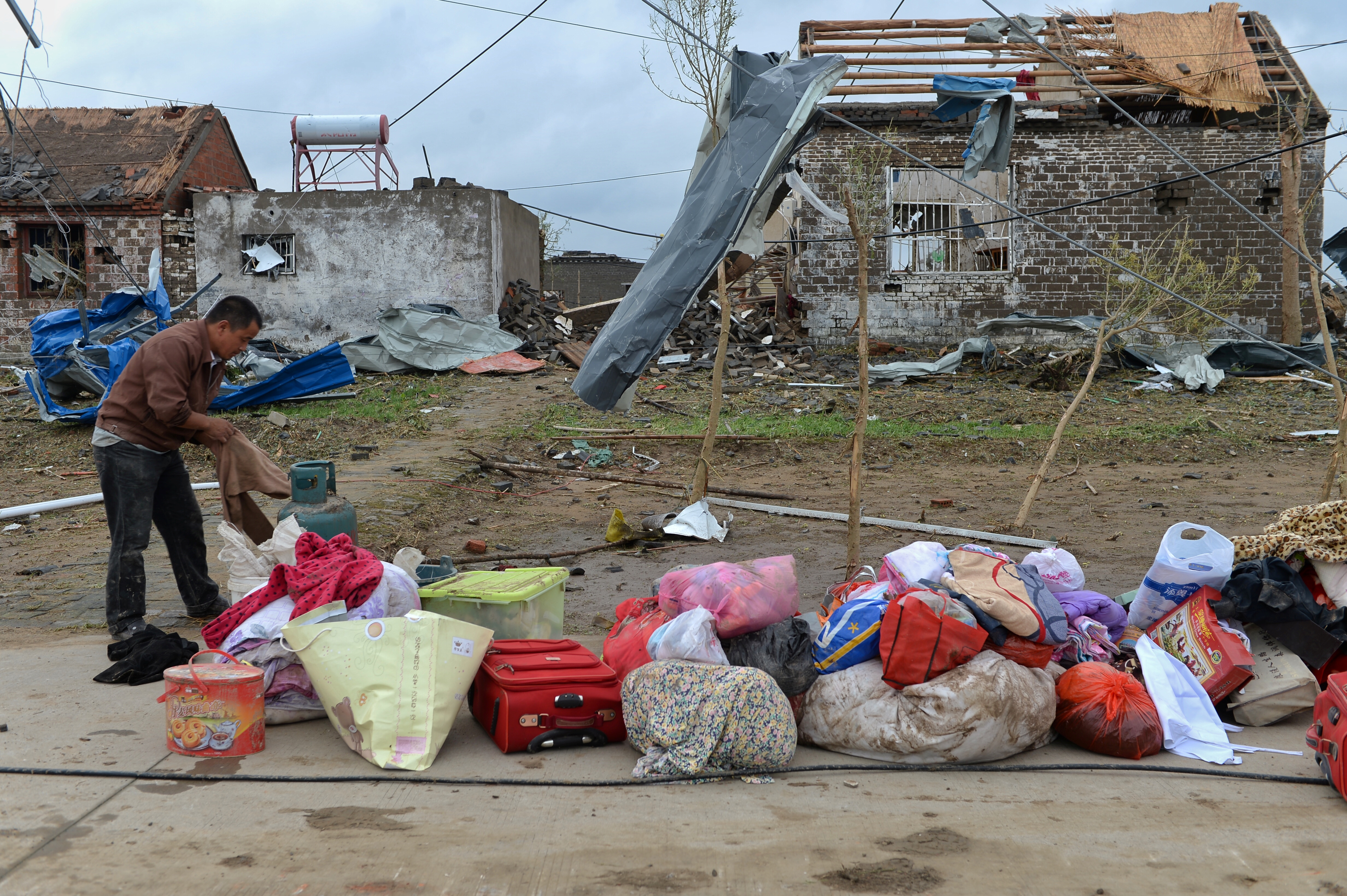 A man takes out his belongings from his damaged house after a tornado hit Funing on Thursday, in Yancheng, Jiangsu province, June 24, 2016.