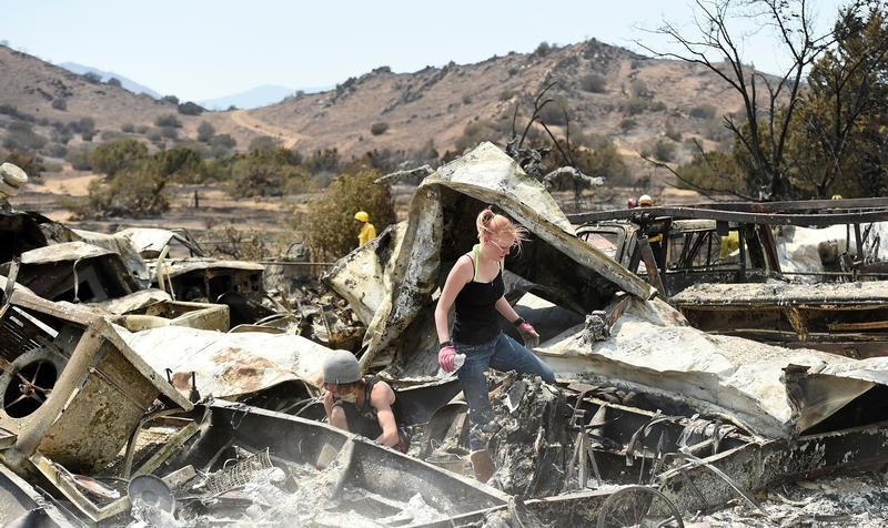 Emily Fryer, 20, searches for family heirlooms at her boyfriend's leveled home after the Erskine Fire burned through South Lake, California, U.S. June 26, 2016