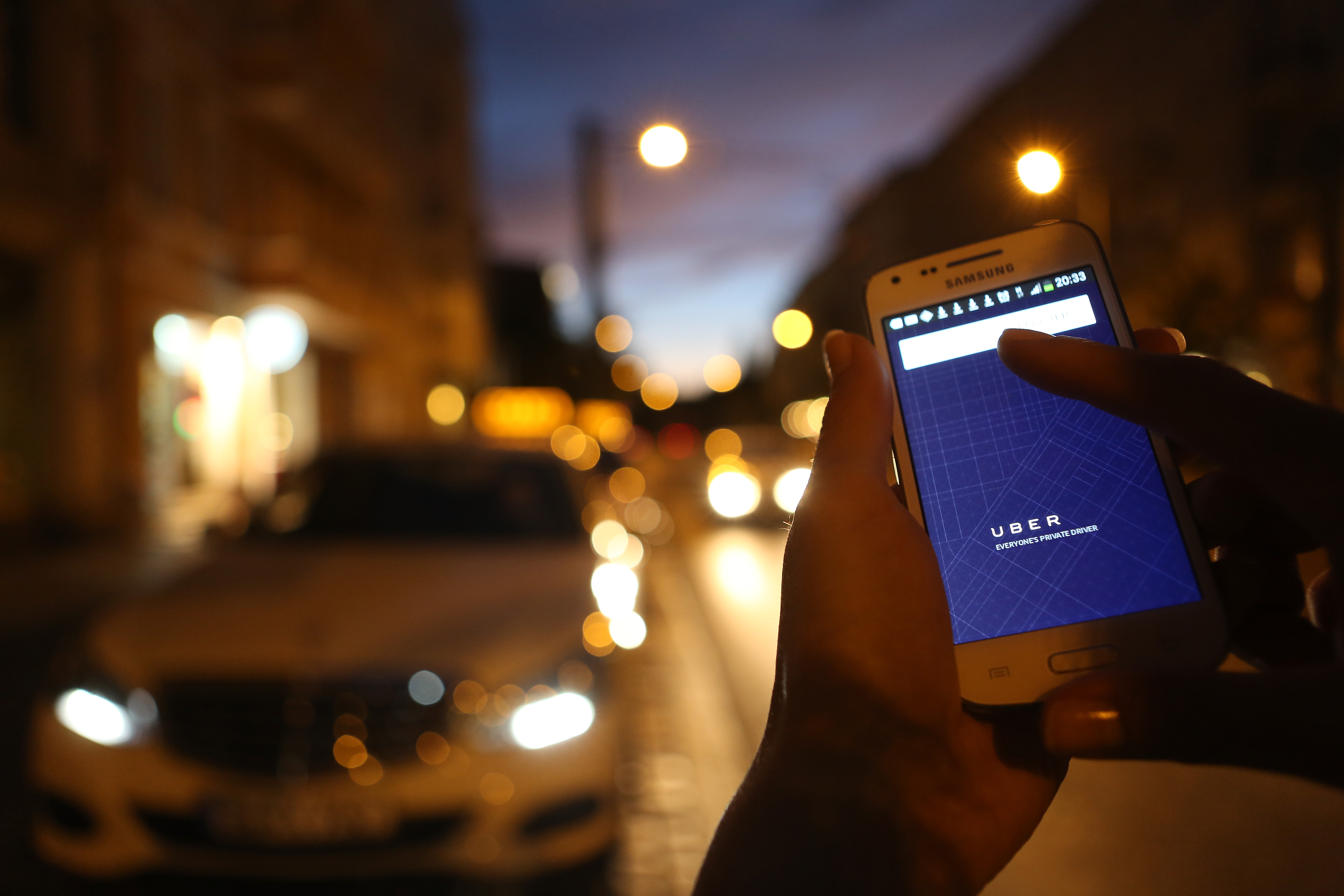 In this photo illustration, a woman uses the Uber app on an Samsung smartphone on September 2, 2014 in Berlin, Germany.