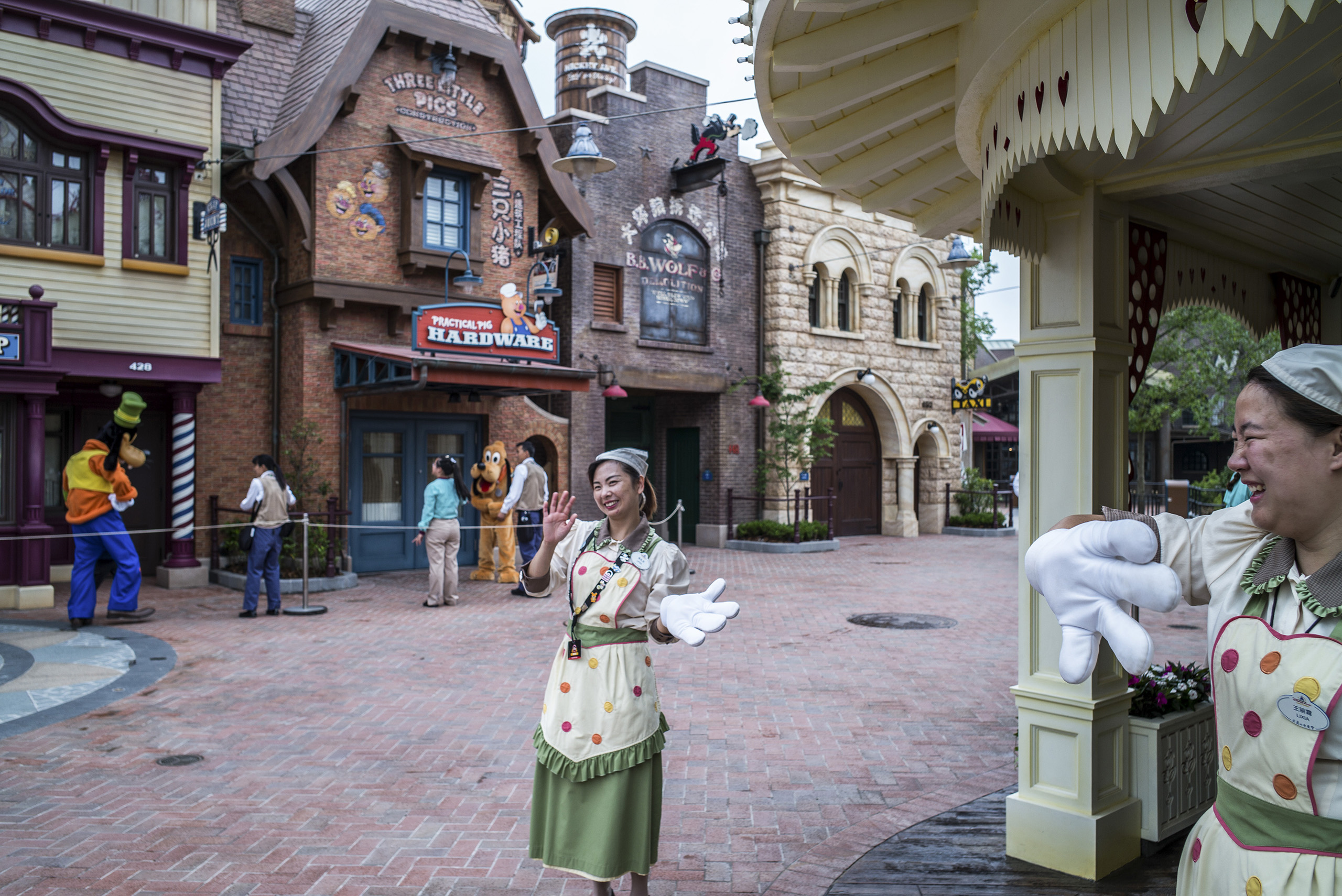 Workers at Shanghai Disneyland greet guests during a preview of the theme park on June 10, 2016