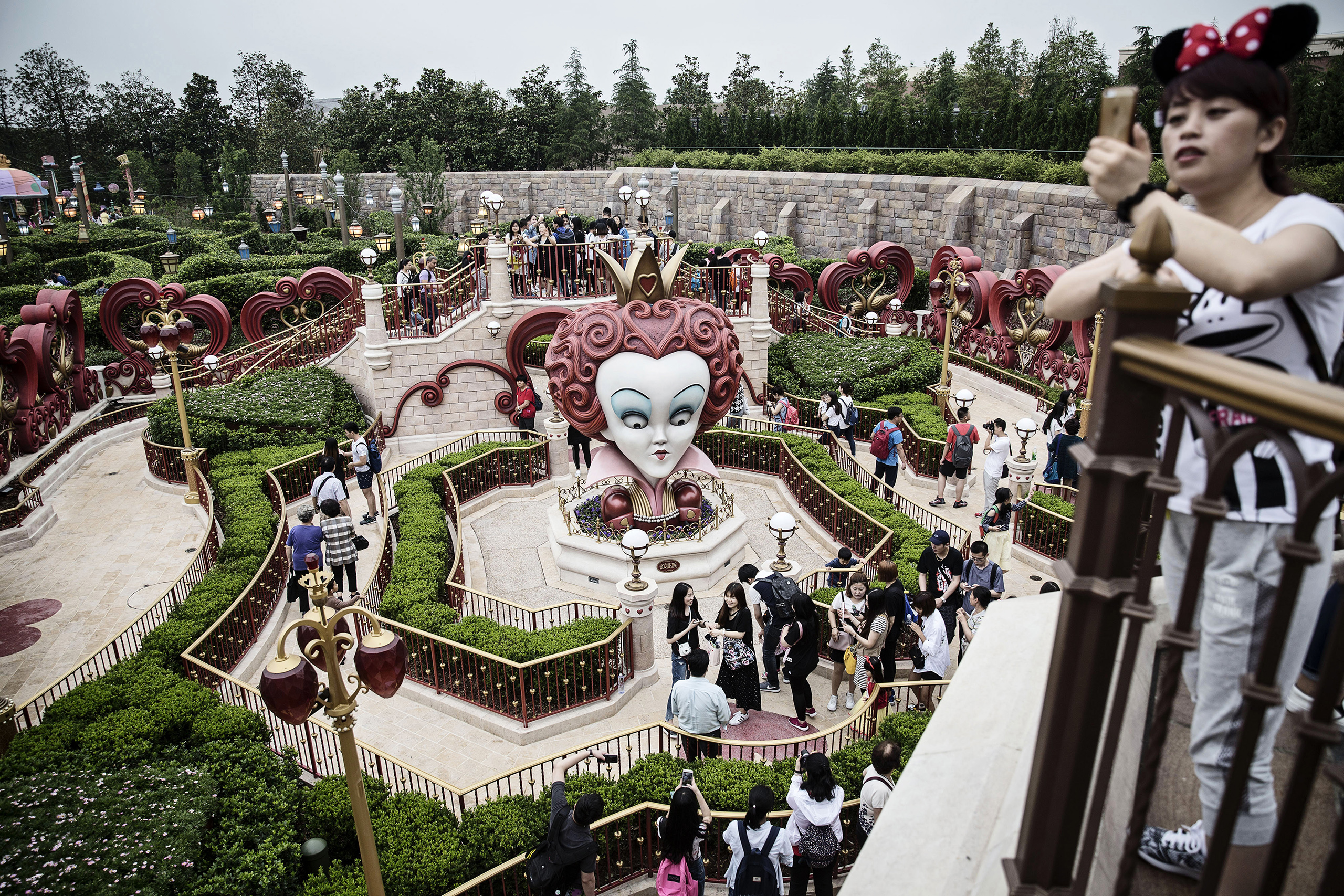 Visitors walk through the Alice in Wonderland Maze on June 8, 2016, during a trial run at Shanghai Disneyland ahead of its official opening