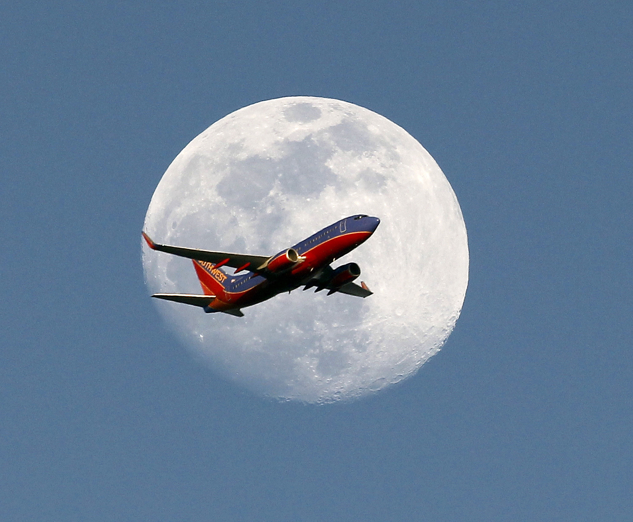 A Southwest Airlines passenger plane crosses the waxing gibbous moon in Whittier, May 30, 2015.