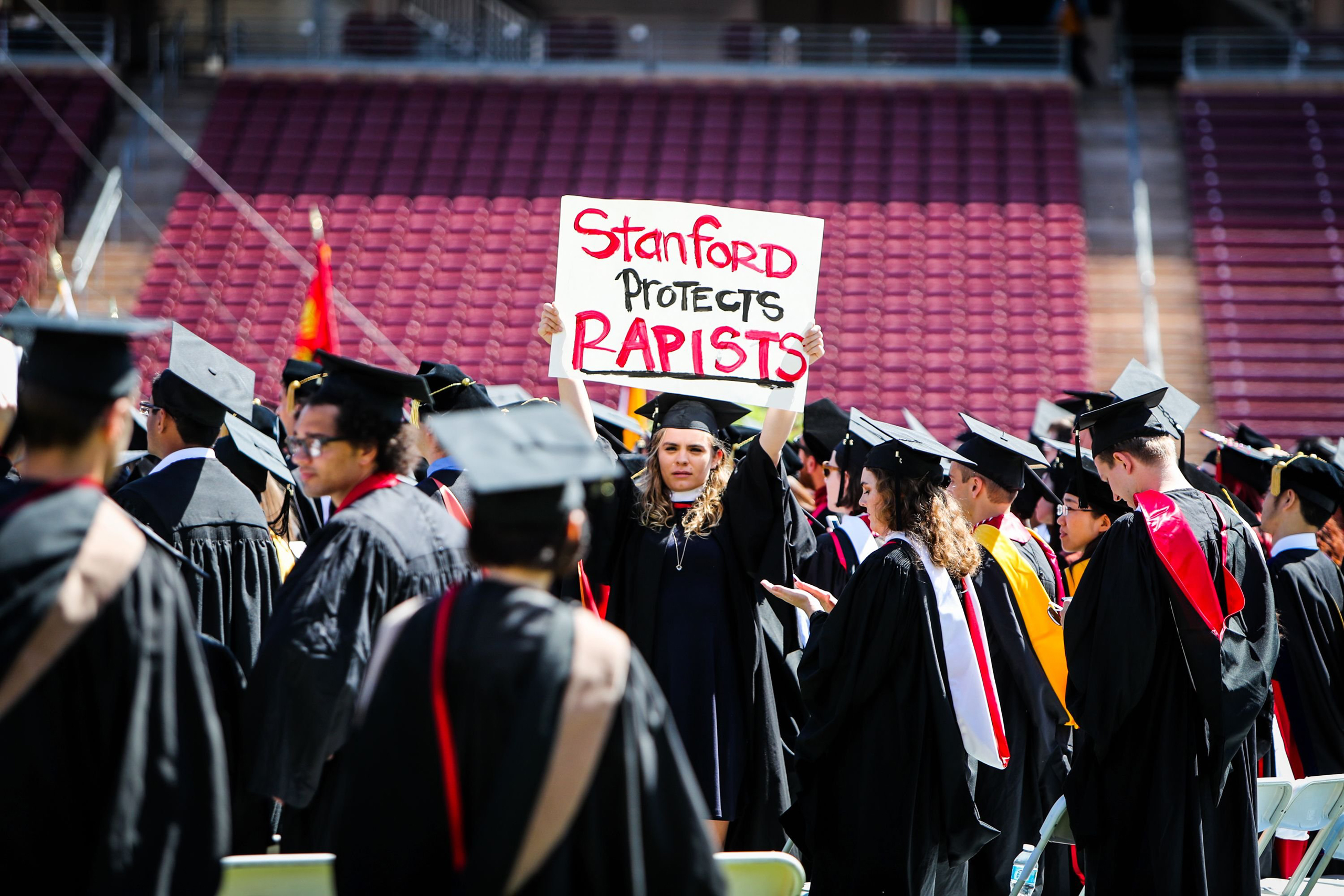 A woman carries a sign in solidarity for a Stanford rape victim during graduation at Stanford University, in Palo Alto, Calif. on June 12, 2016.