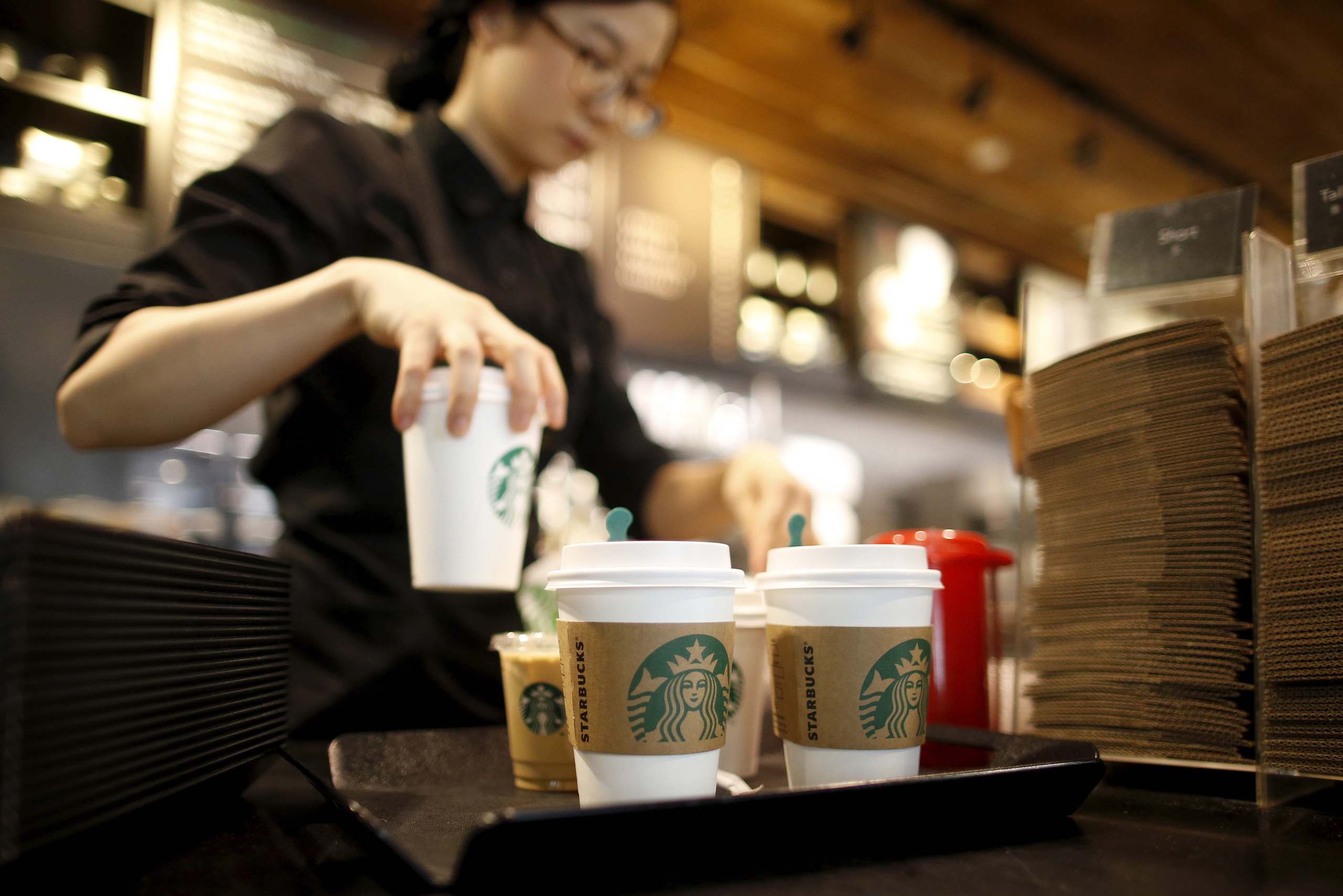 A staff serves beverages at a Starbucks coffee shop in Seoul on Mar. 7, 2016.