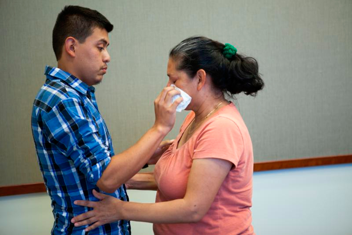 Steve Hernandez wipes a tear from his mother's eye after seeing her for the first time in 20 years in San Diego, Calif., on June 9, 2016.