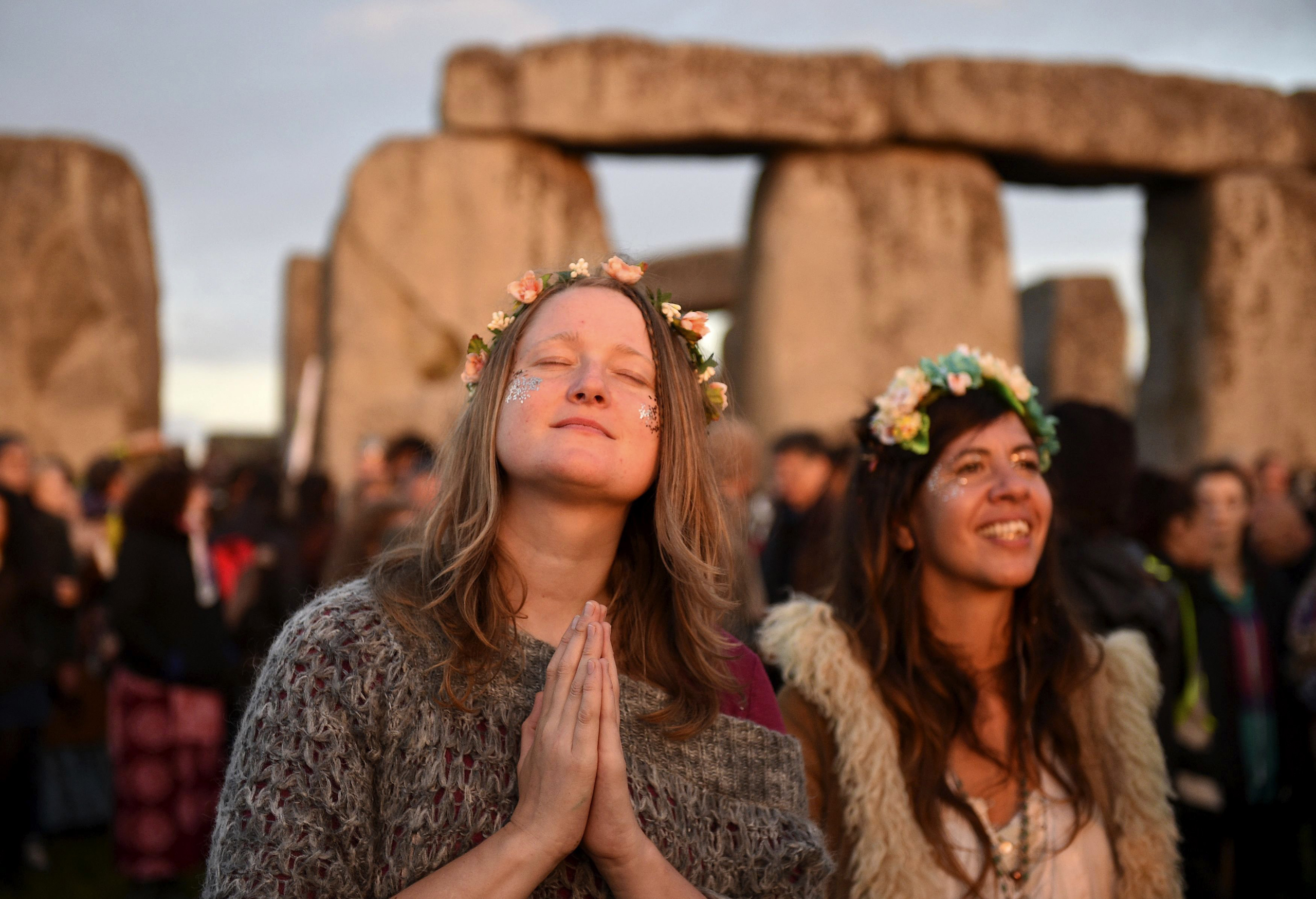 People gather to see the sun rise at the ancient stone circle Stonehenge, during the Summer Solstice, the longest day of the year, in Wiltshire, United Kingdom, June 21, 2016.