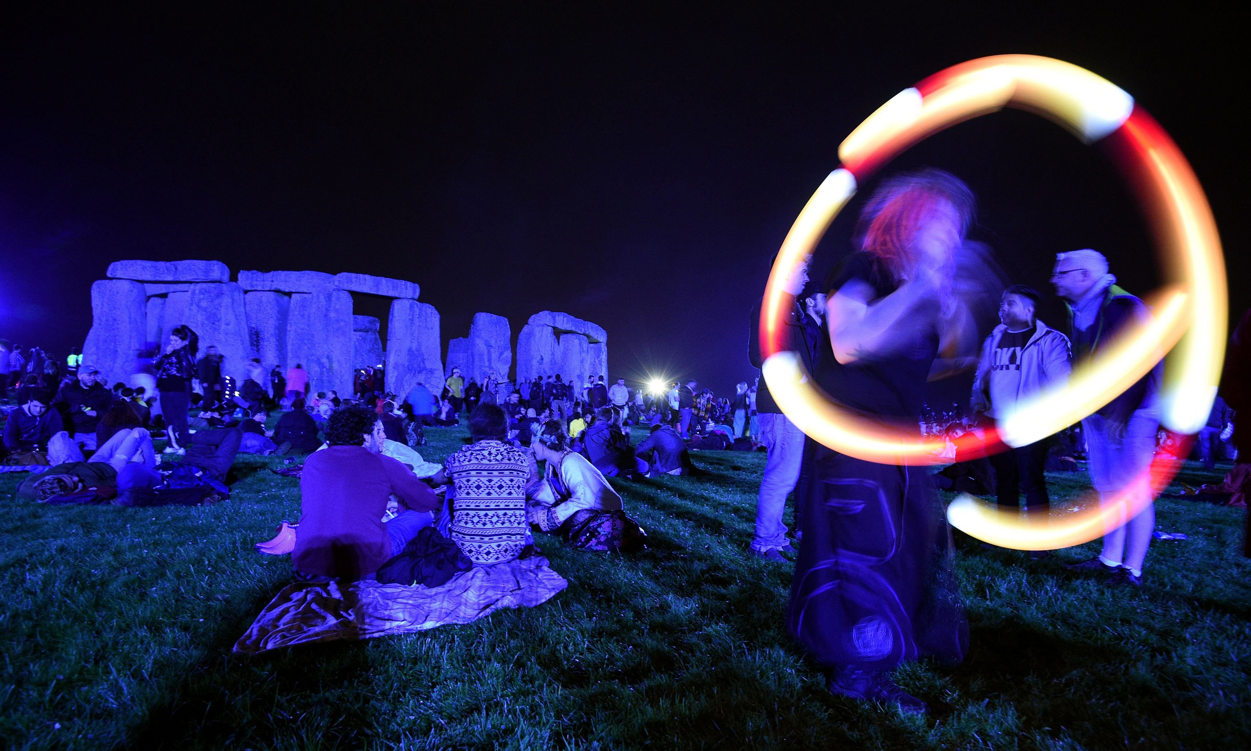 A poi performer spins light balls as people gather at Stonehenge in Wiltshire, England to see in the new dawn after this year's Summer Solstice on June 21, 2016.