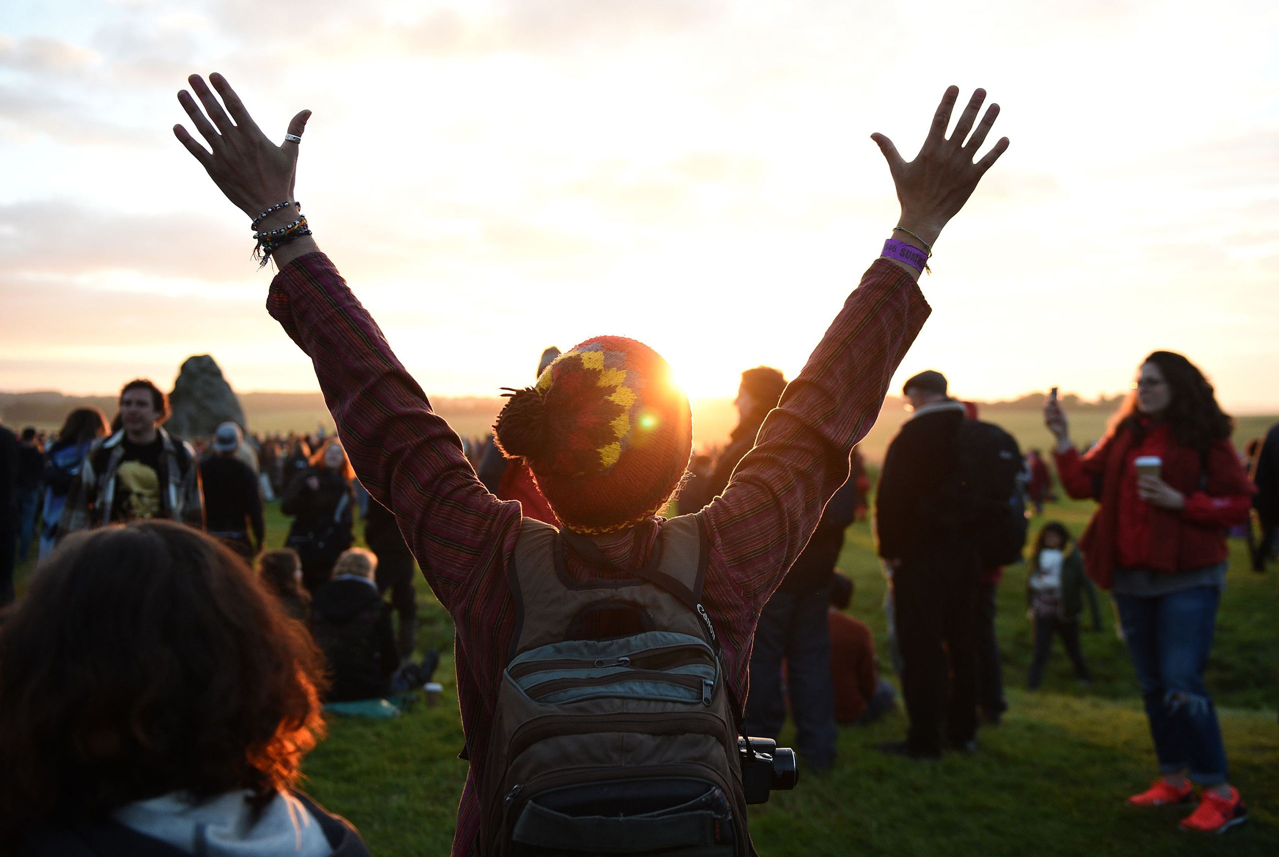 People watch the sun rise at Stonehenge in Wiltshire as they see in the new dawn during this year's Summer Solstice, June 21, 2016.