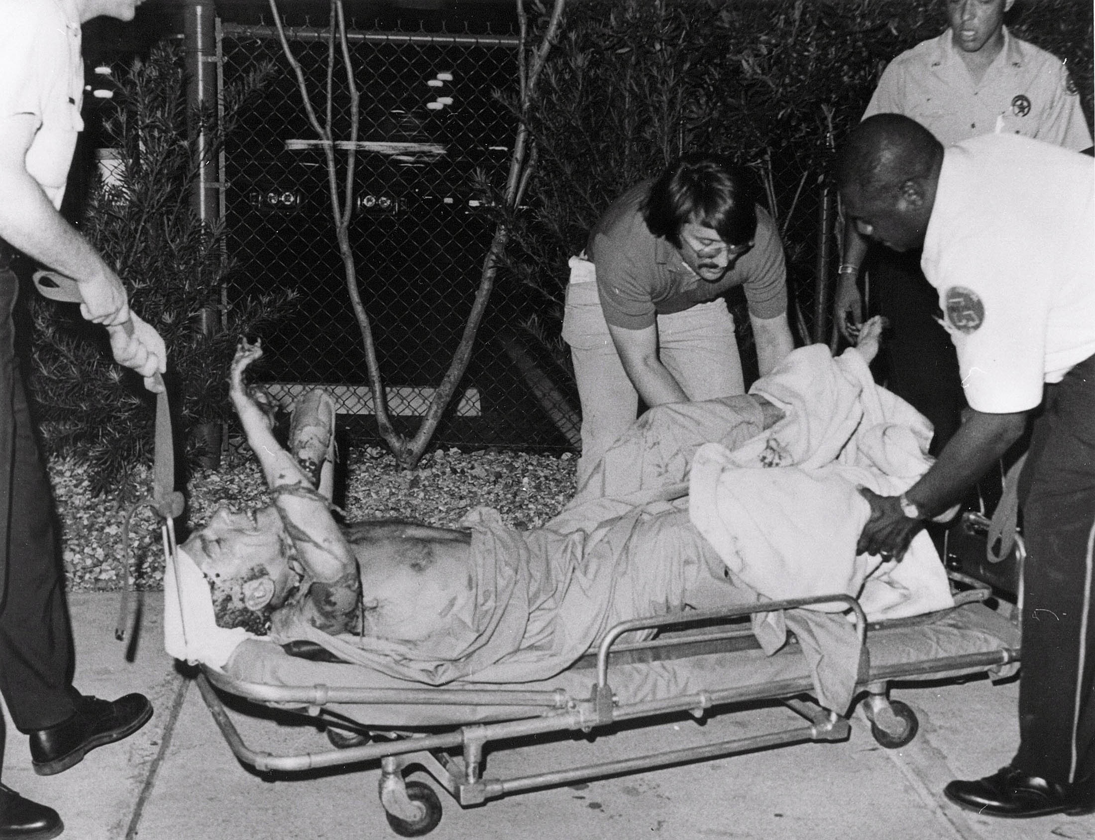 Luther Boggs being helped on to a stretcher.