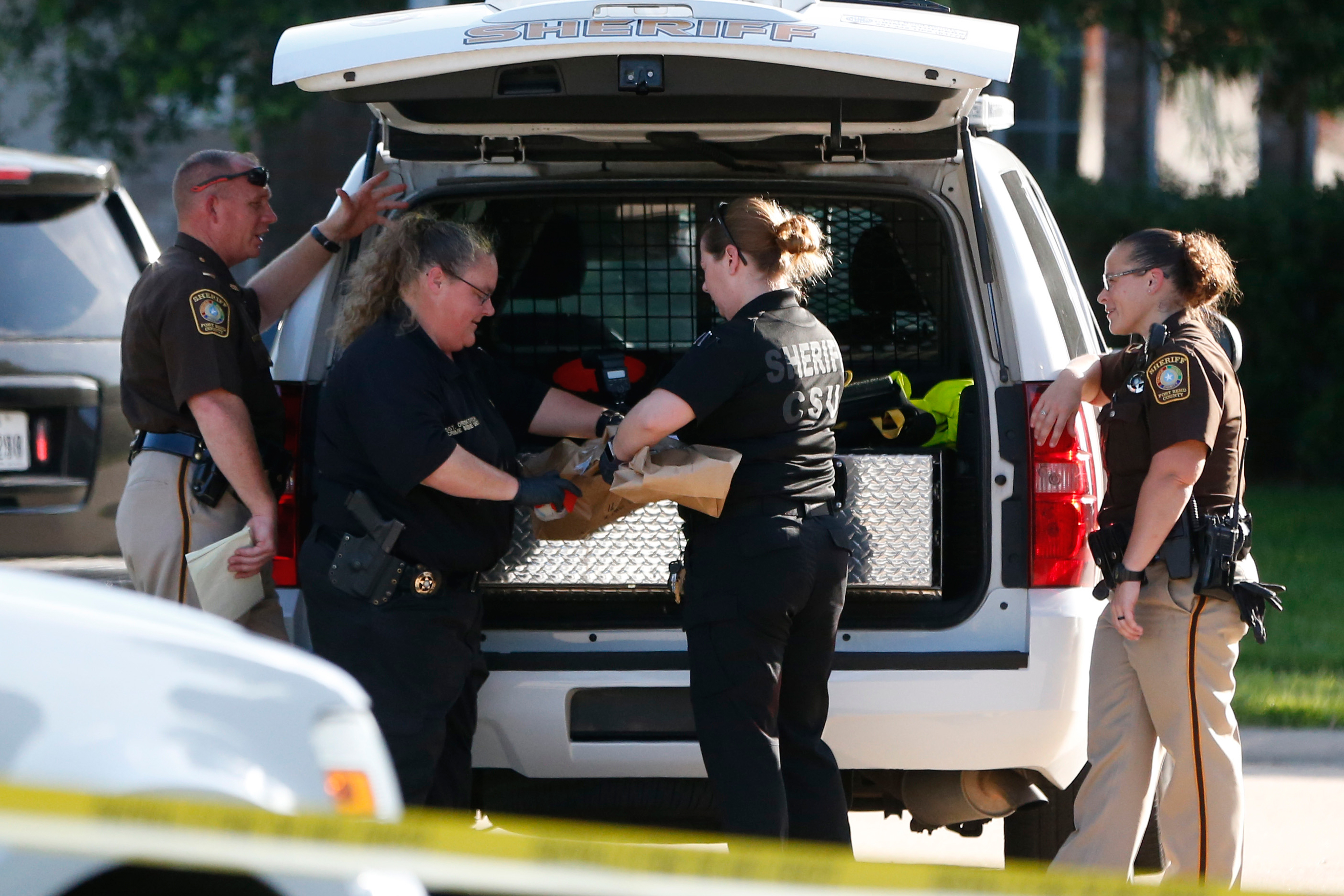 Fort Bend County Sheriffs department crime scene members bag a gun for evidence in a shooting at Blanchard Grove and Remson Hollow in Katy, Texas on June 24, 2016.