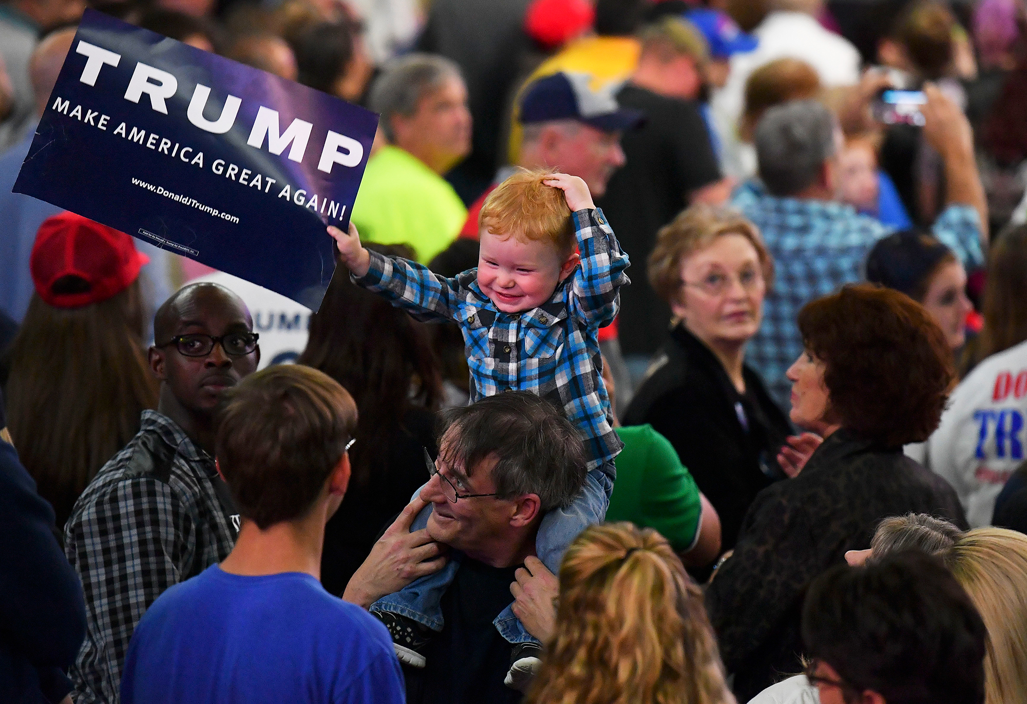 A child waves a Trump sign before Republican presidential candidate Donald Trump addresses his supporters during a rally at on May 5, 2016 in Charleston, W.V.