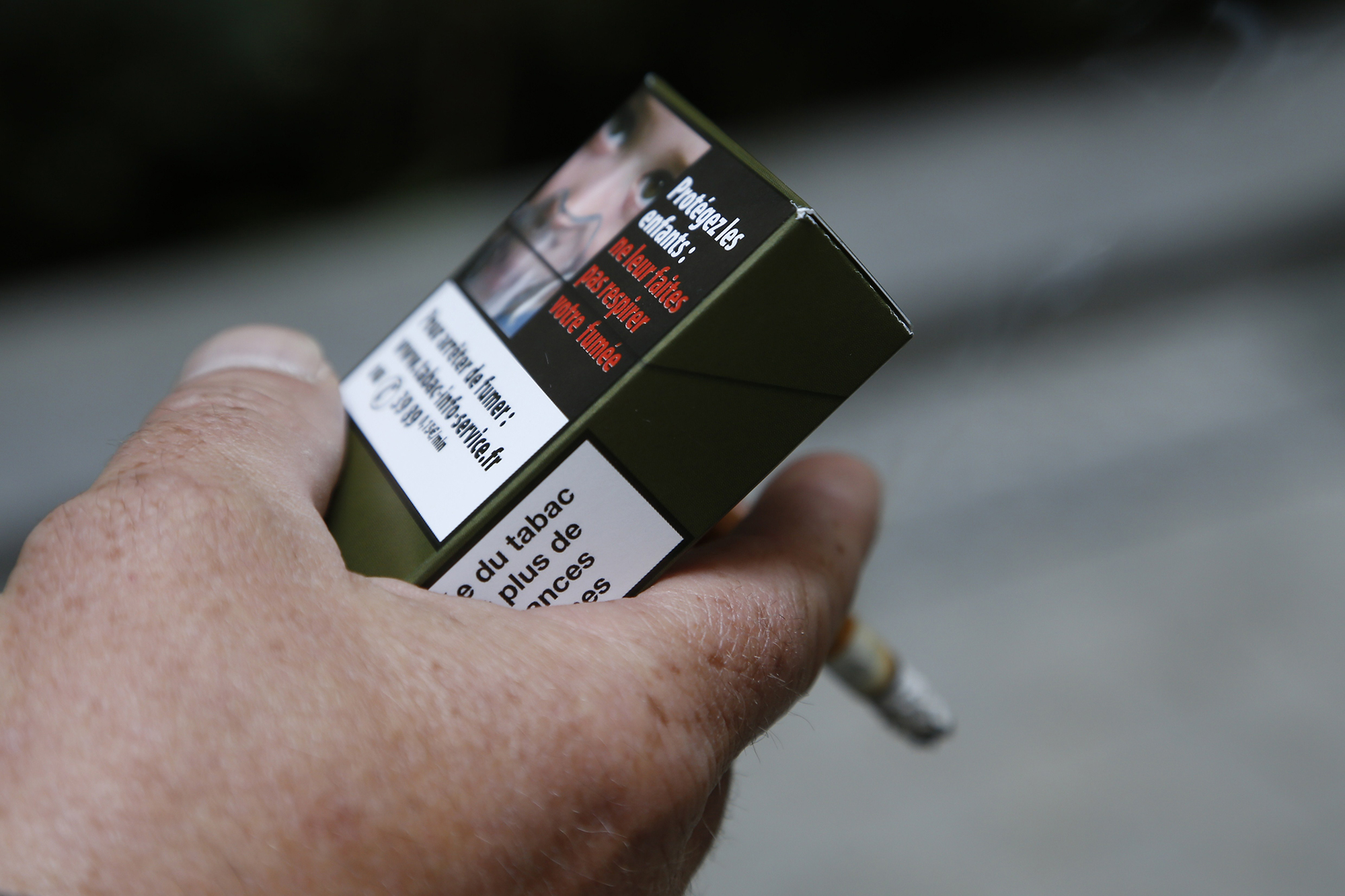 A man smokes a cigarette on September 25, 2014 in Paris, holding a sample of a  plain cigarette packaging  cigarette box (THOMAS SAMSON/AFP/Getty Images)