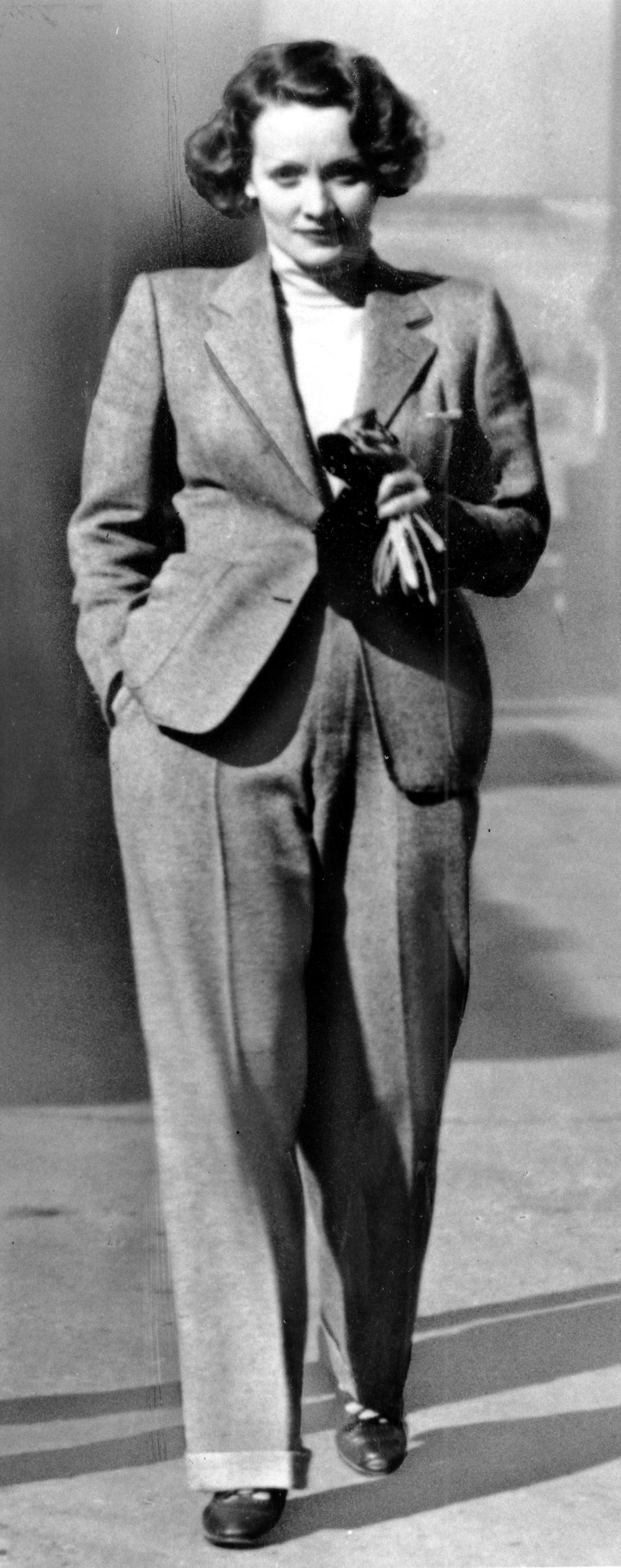 Actress Marlene Dietrich wears a trendsetting masculine style pant suit created by French couturiere Coco Chanel in 1933.
