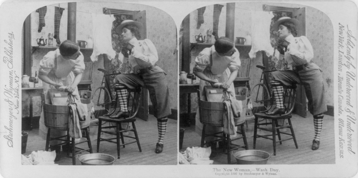 Stereograph card of  The New Woman   with cigarette in mouth, wearing pants, hat, and gloves, standing with one foot on chair and facing a man wearing a dress and doing laundry, circa 1897.