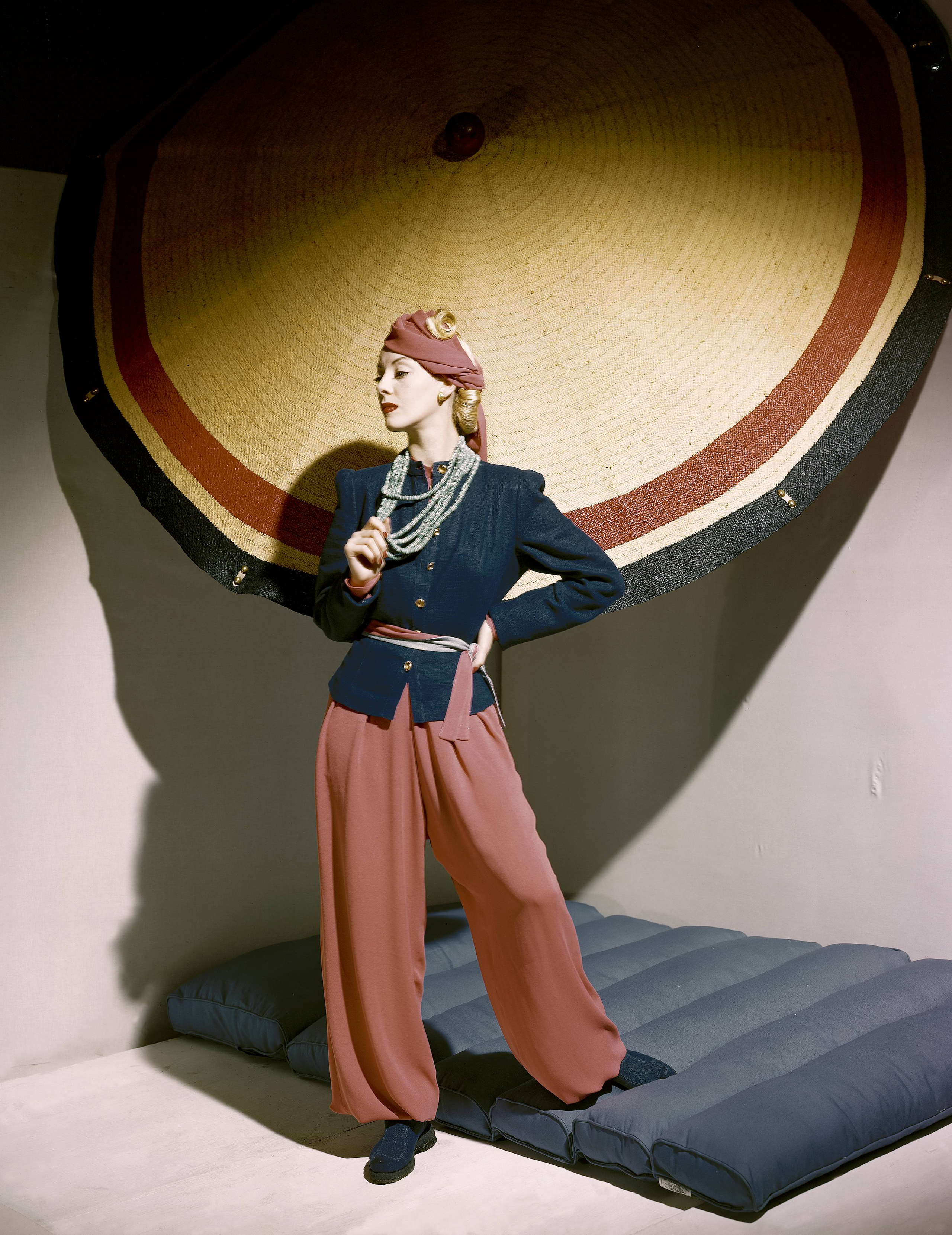 Model standing next to umbrella, wearing blue linen jacket and silk crepe pyjamas with double-layered trousers, 1939.