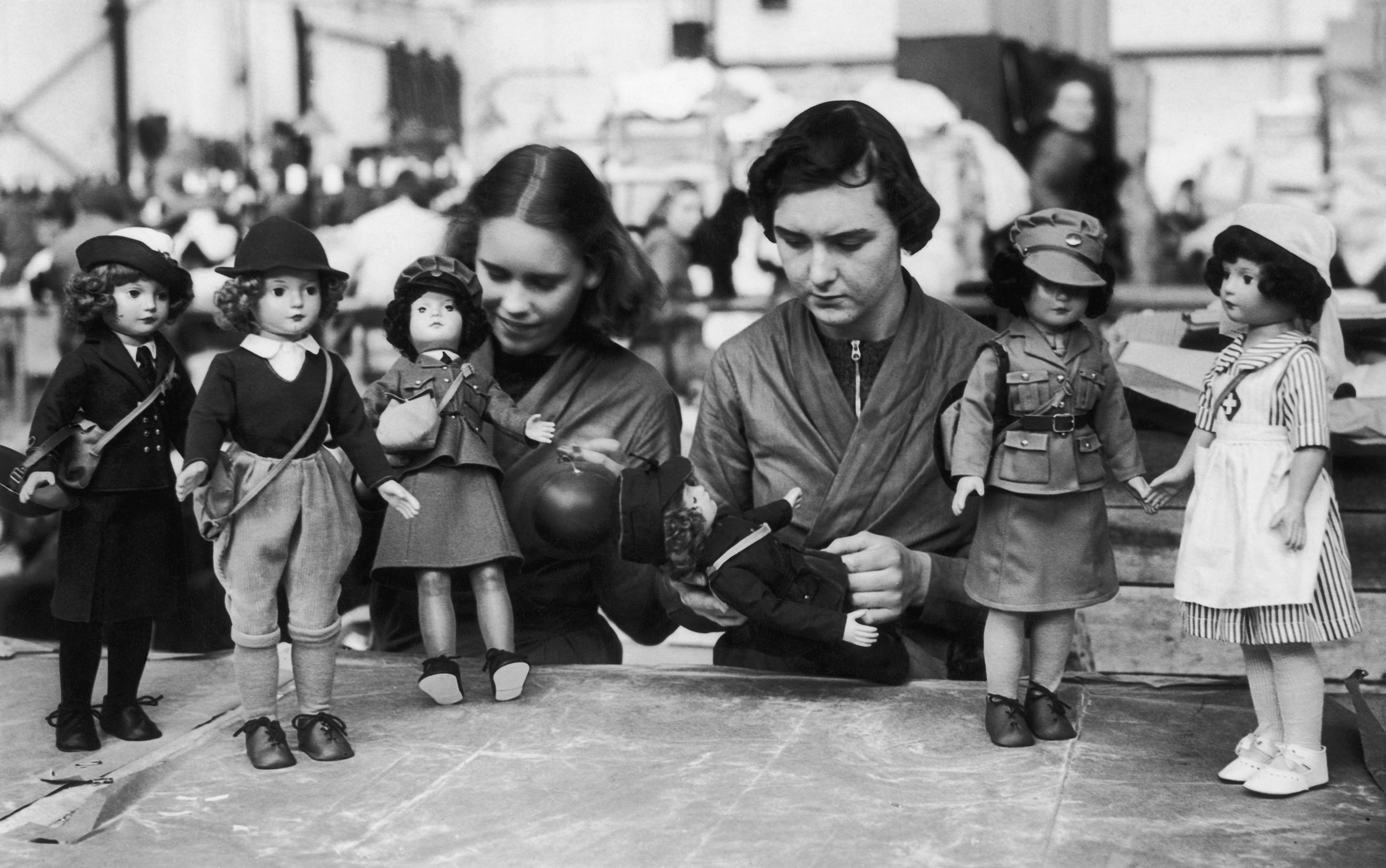 Workers in a British toy factory with dolls dressed in the uniforms of various women's war services—including a style with pants—on Oct. 19, 1939. The toys are being produced in time for the first Christmas of the war.