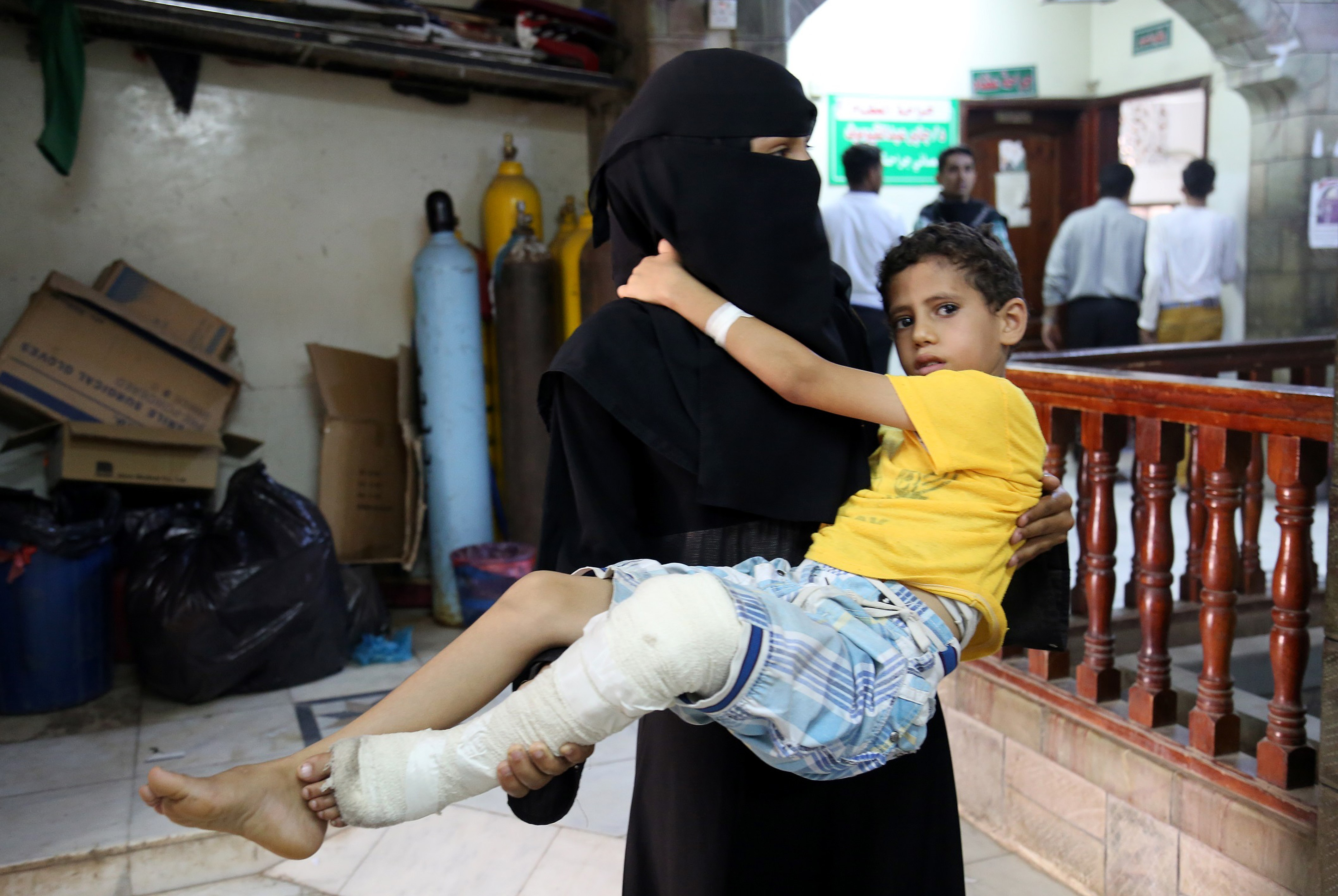 A woman carries a boy who has been injured in a Shiite Houthi attack, targeting residential areas, to es-Sevra hospital, in Taiz, Yemen, on June 4, 2016.