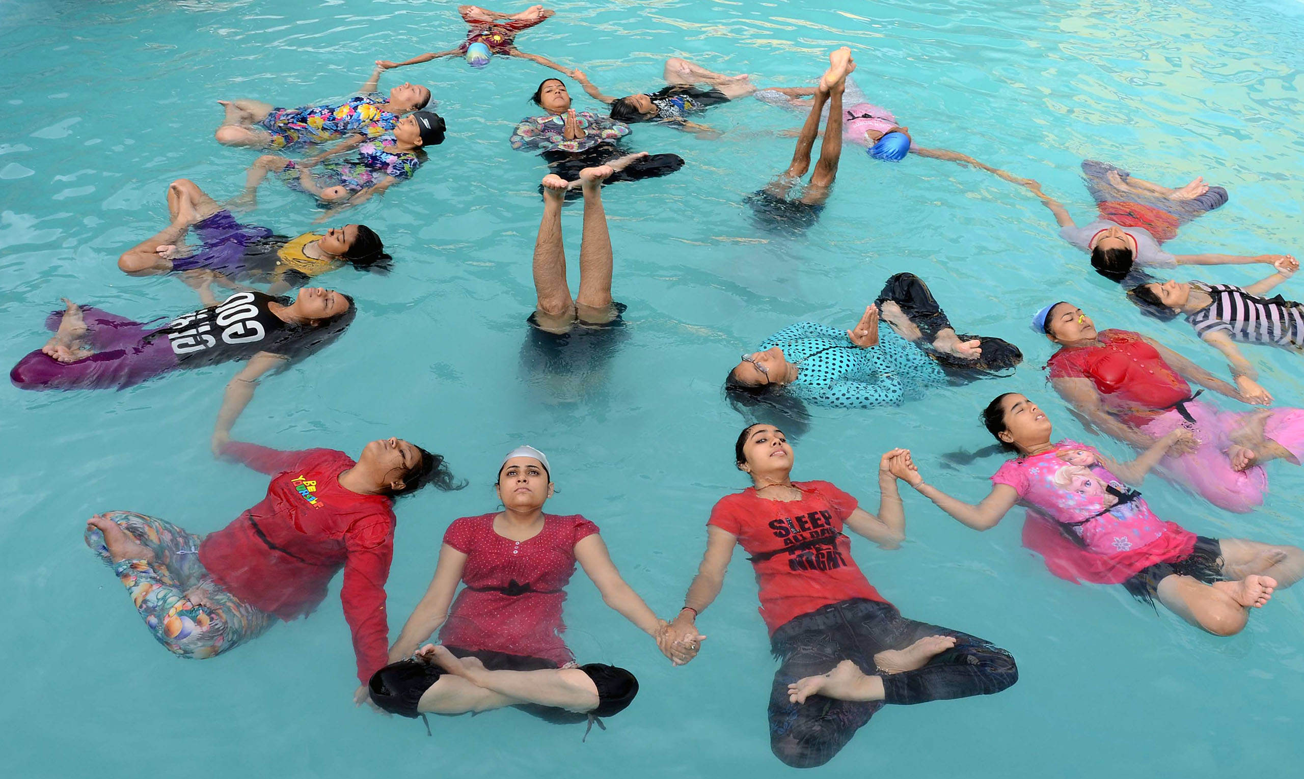 Indian yoga practitioners take part in a yoga session in a swimming pool on International Yoga Day in Jodhpur, India, on June 21, 2016.