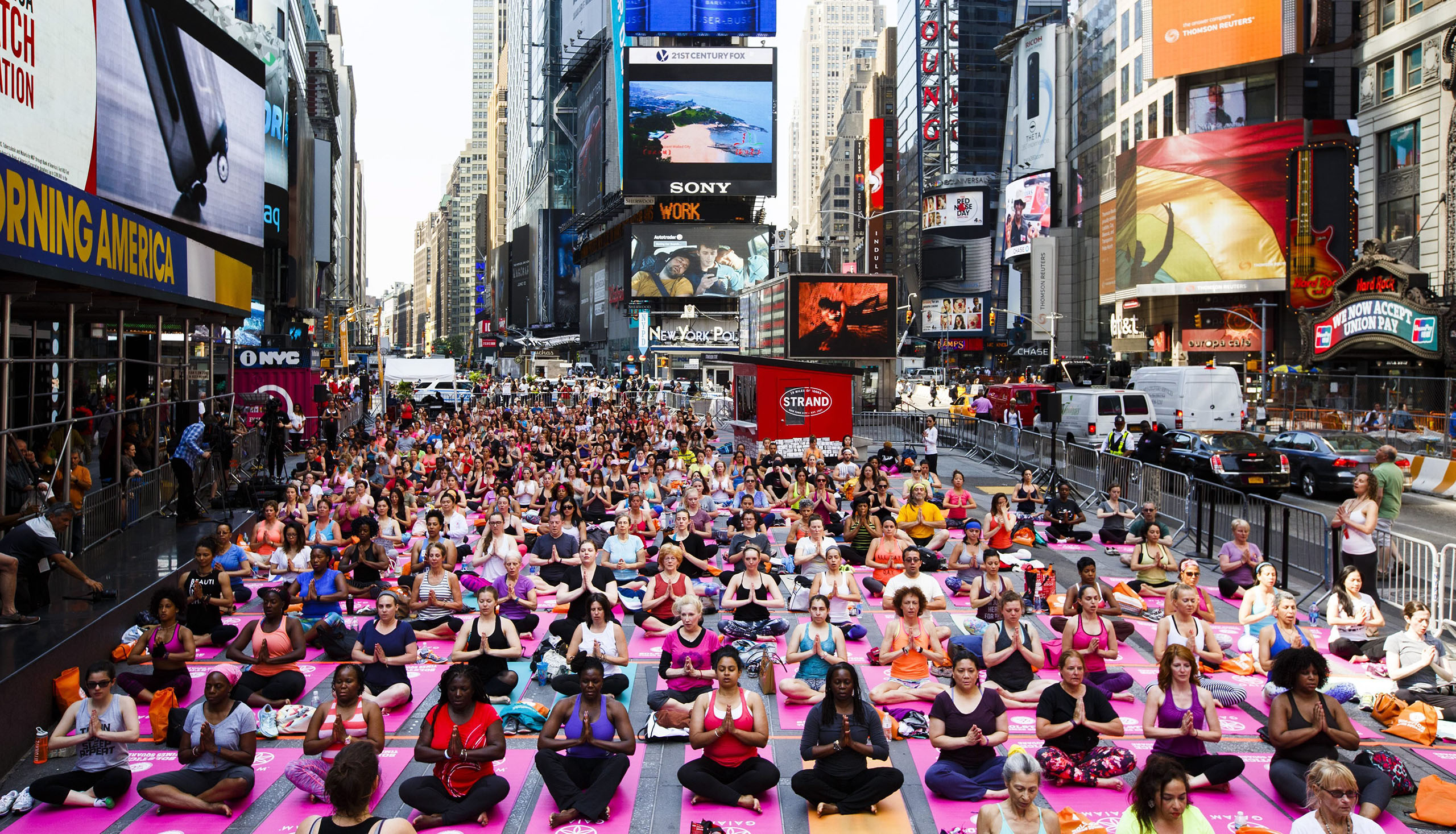 People participate in a group yoga class in Times Square as part of the 14th annual 'Solstice in Times Square: Mind Over Madness Yoga' to mark the summer solstice in New York, New York, June 20, 2016.